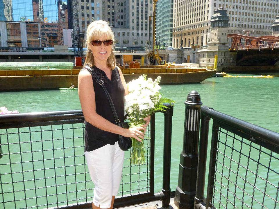 Susan Decker of Arlington Heights, a granddaughter of an Eastland survivor and the co-founder of the Eastland Disaster Historical Society, holds flowers before they are placed in the river.