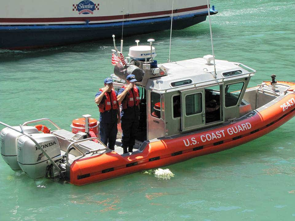 Members of the U.S. Coast Guard place a bouquet in the Chicago River about the spot where the Eastland overturned 99 years ago on July 24, 1915. The Coast Guard was involved with the rescue of more than 1,600 people, while 844 died.