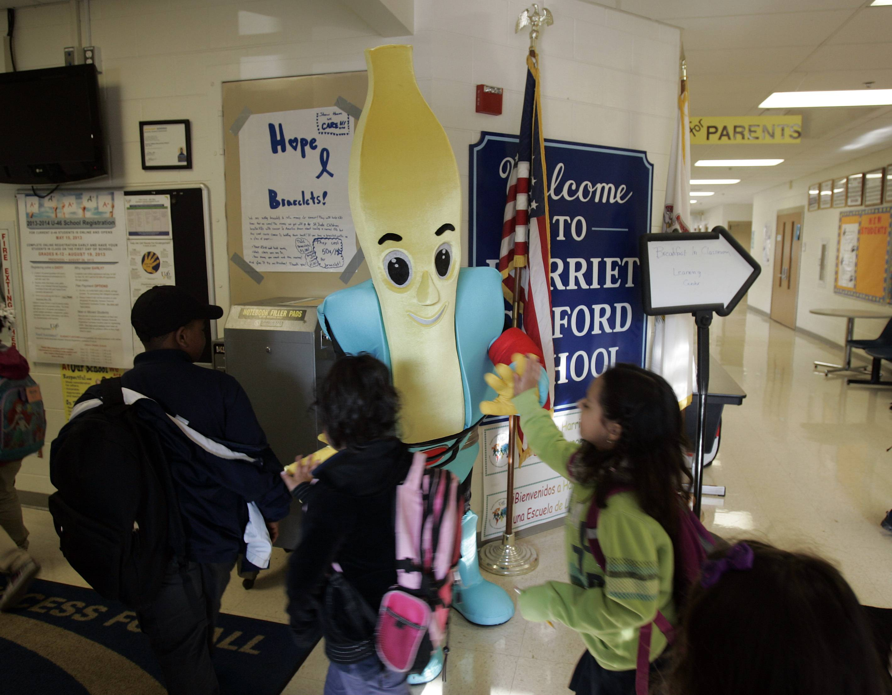 Captain Nutrition greets students at Harriet Gifford Elementary School in Elgin as they head to the classroom to enjoy breakfast as part of the Breakfast in Classroom program that is available at 10 U46 schools this year. Elgin Area School District U-46 teachers are trying to revive a special program that fed students a free breakfast in their classrooms.