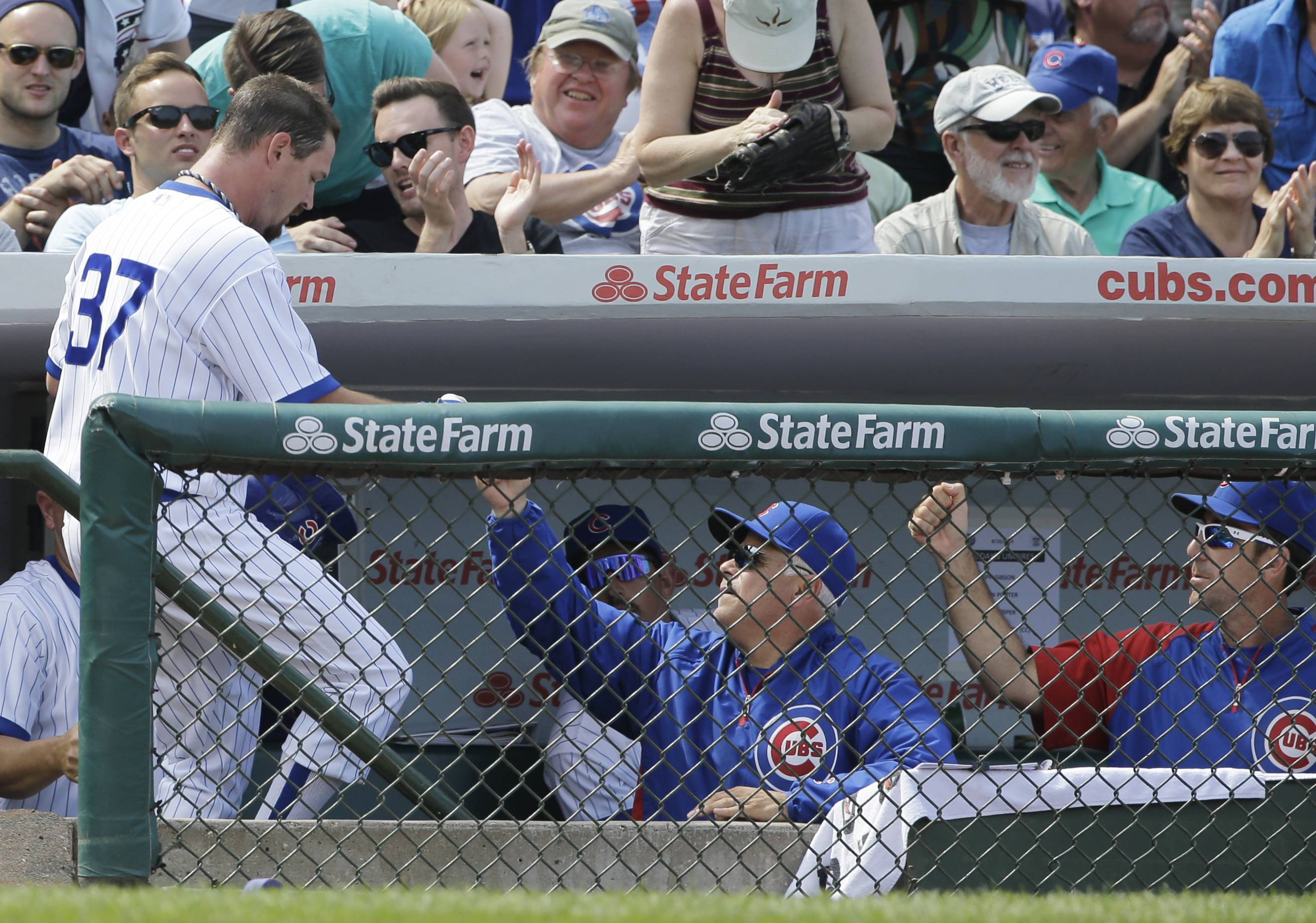 Chicago Cubs' Travis Wood, left, celebrates with manager Rick Renteria after scoring on a single hit by Javier Baez during the fifth inning of an interleague baseball game Sunday against the Tampa Bay Rays in Chicago.