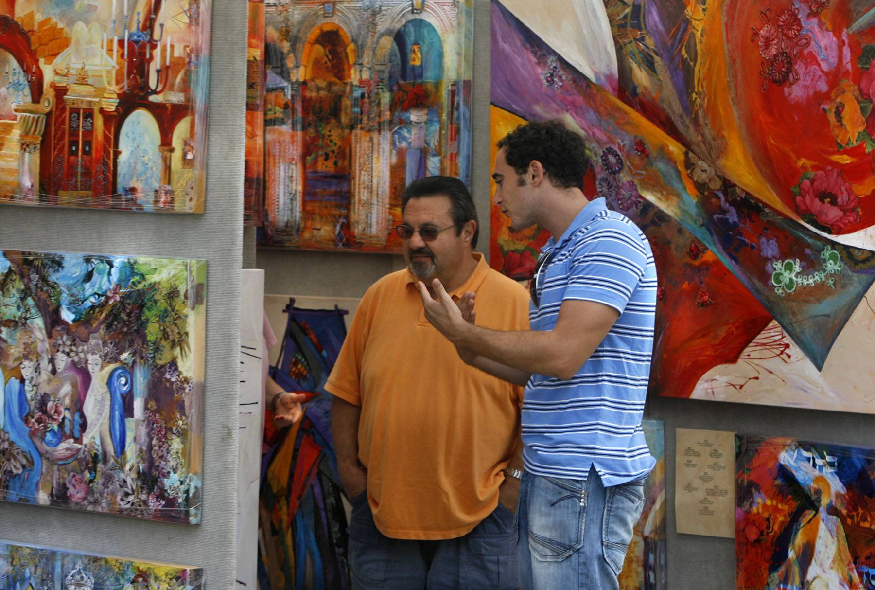 Smadar Livne of Baltimore explains his paintings to Bo Kuriniec of Deerfield at the 13th Annual Lincolnshire Art Festival. The festival marks its 17th year in 2014.
