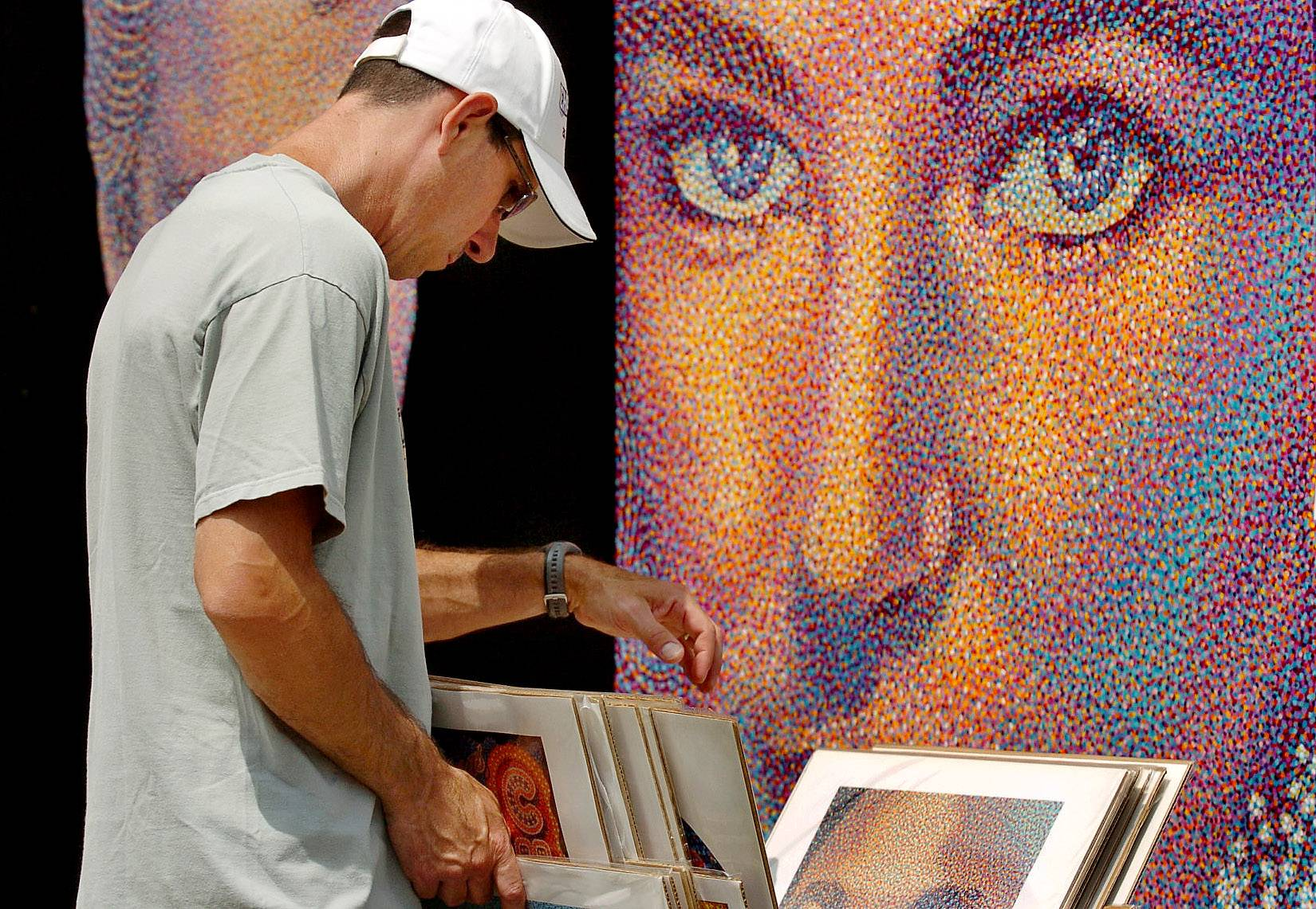 Steve Poklop of Palatine is under the watchful eyes of Elizabeth Taylor as he peruses the Pop Pointillism paintings of artist Tim McWilliams of Atlanta, Georgia, at a previous Lincolnshire Art Festival. This year's event will be Aug. 16 and 17.