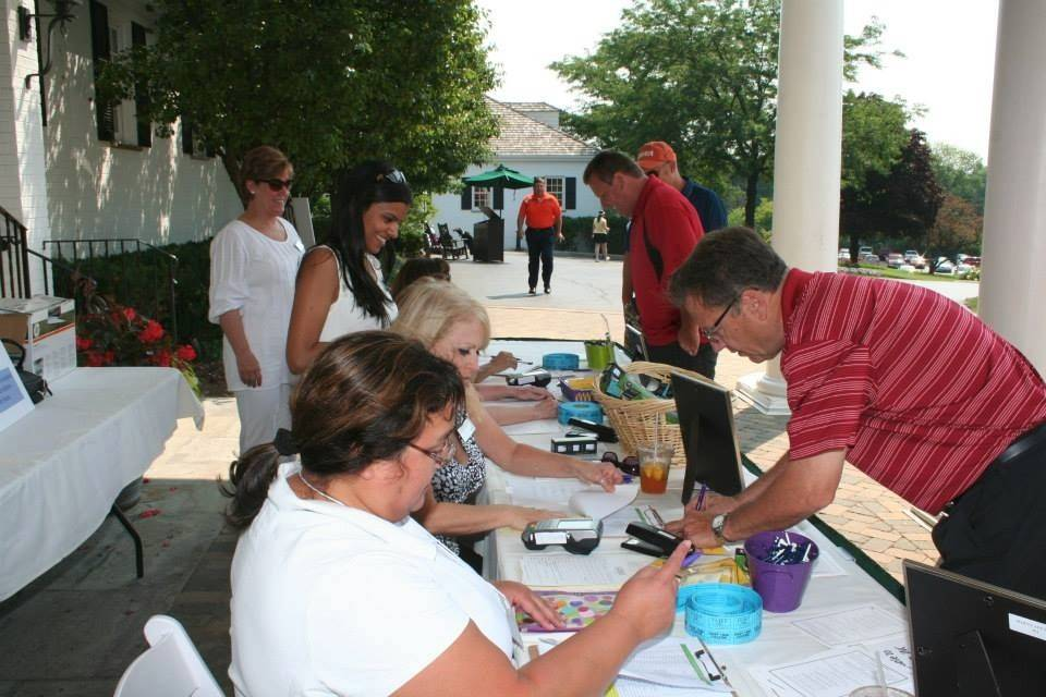 Guests register at the eighth annual WINGS golf outing at the Inverness Golf Club.