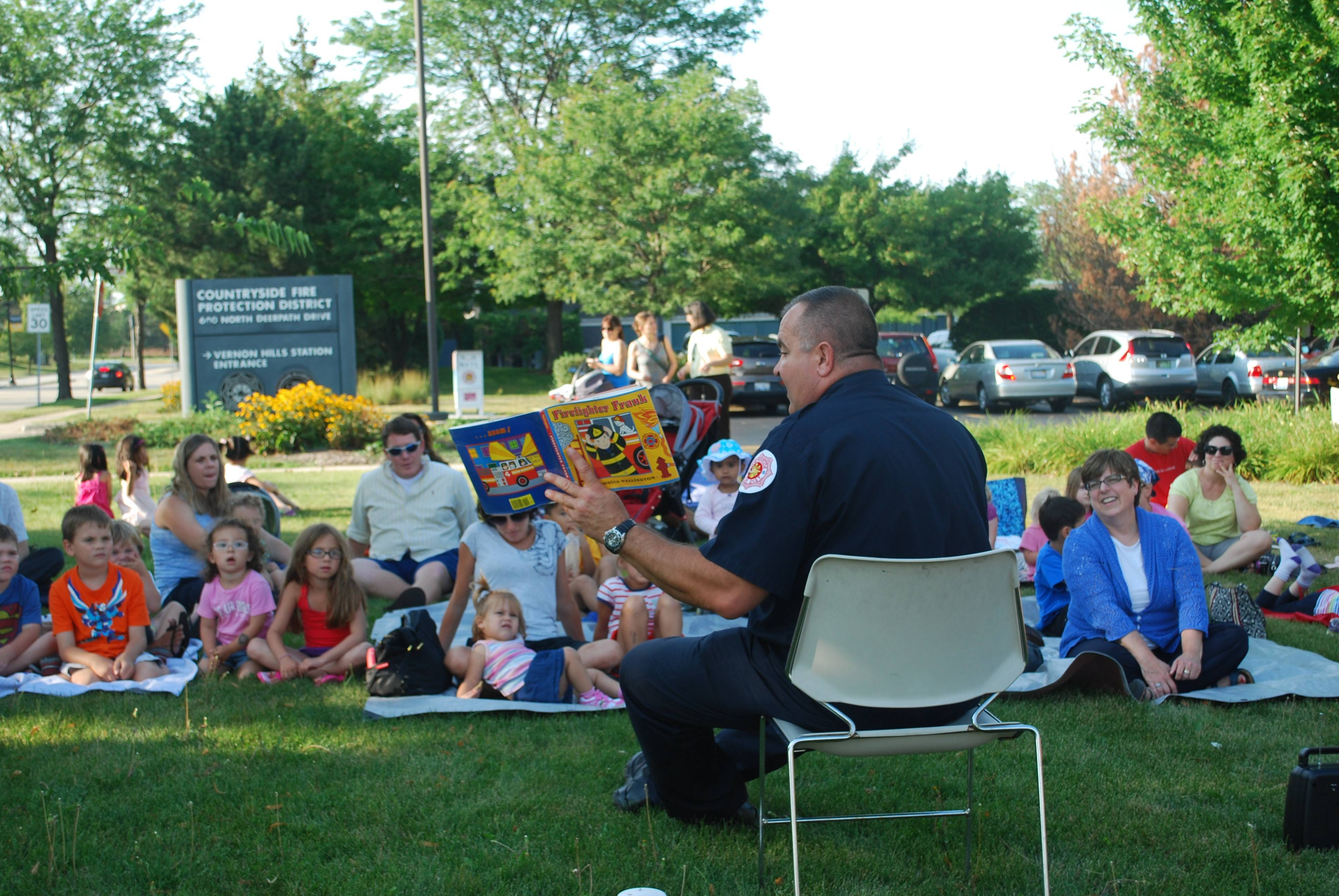 "Fireman Tony Rodkey of Countryside Fire District reads ""Firefighter Frank"" to Cook Memorial Public Library District residents on the front lawn of the firehouse."