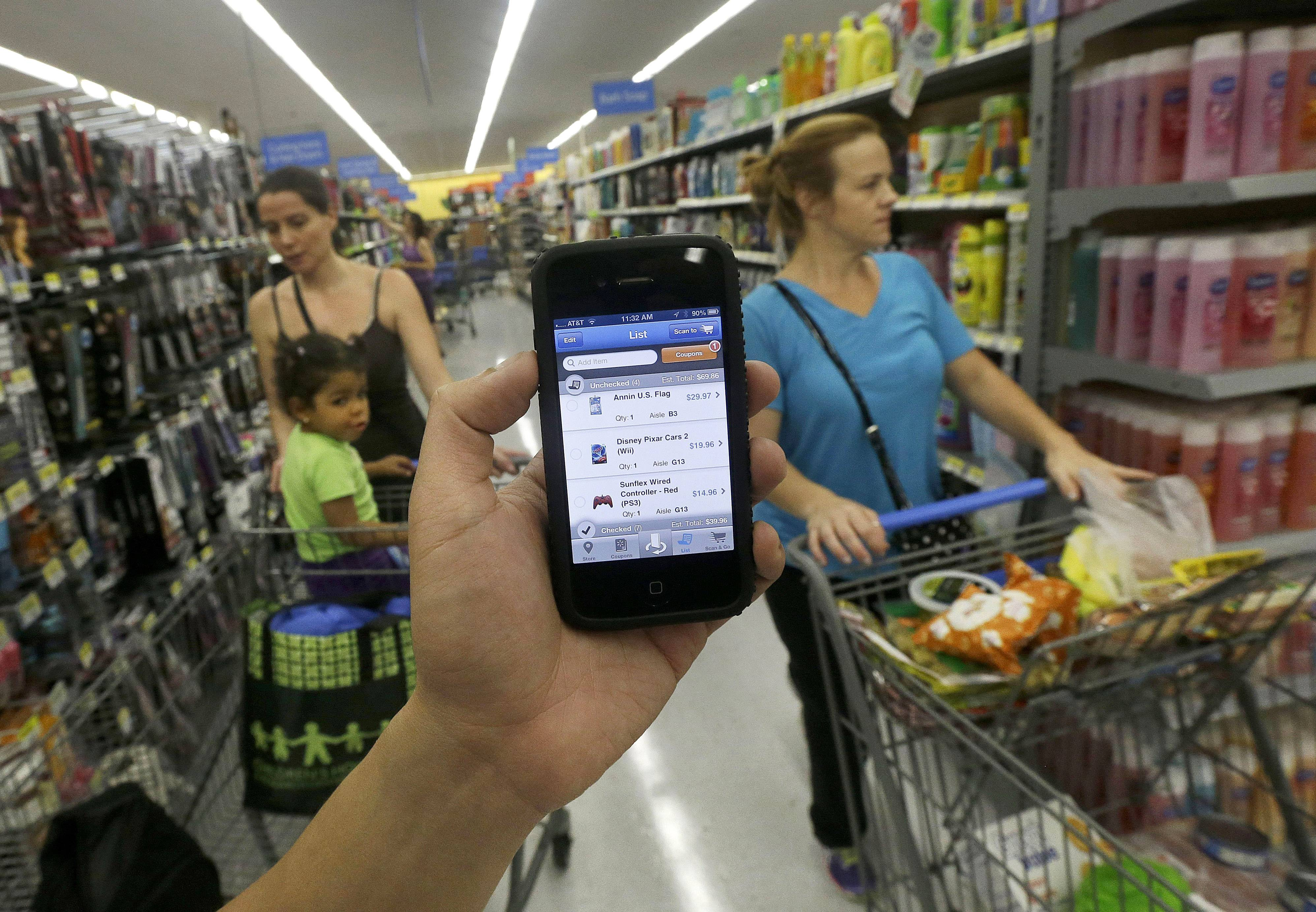 "A Wal-mart representative demonstrates the now-discontinued Scan & Go mobile application on a smartphone at a Wal-mart store. Instead of looking at the app as a failure, Wal-Mart took what it learned from ""Scan & Go"" to create another service."