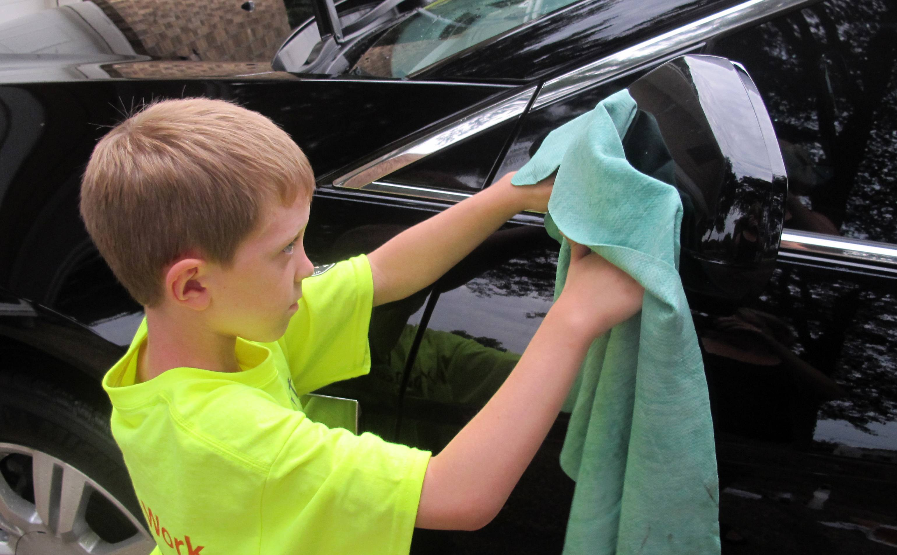 Sterling Murset washes a car at the home of Todd Blanchieri in Pensacola, Fla. The Murset family toured the country this summer doing chores for families in need.