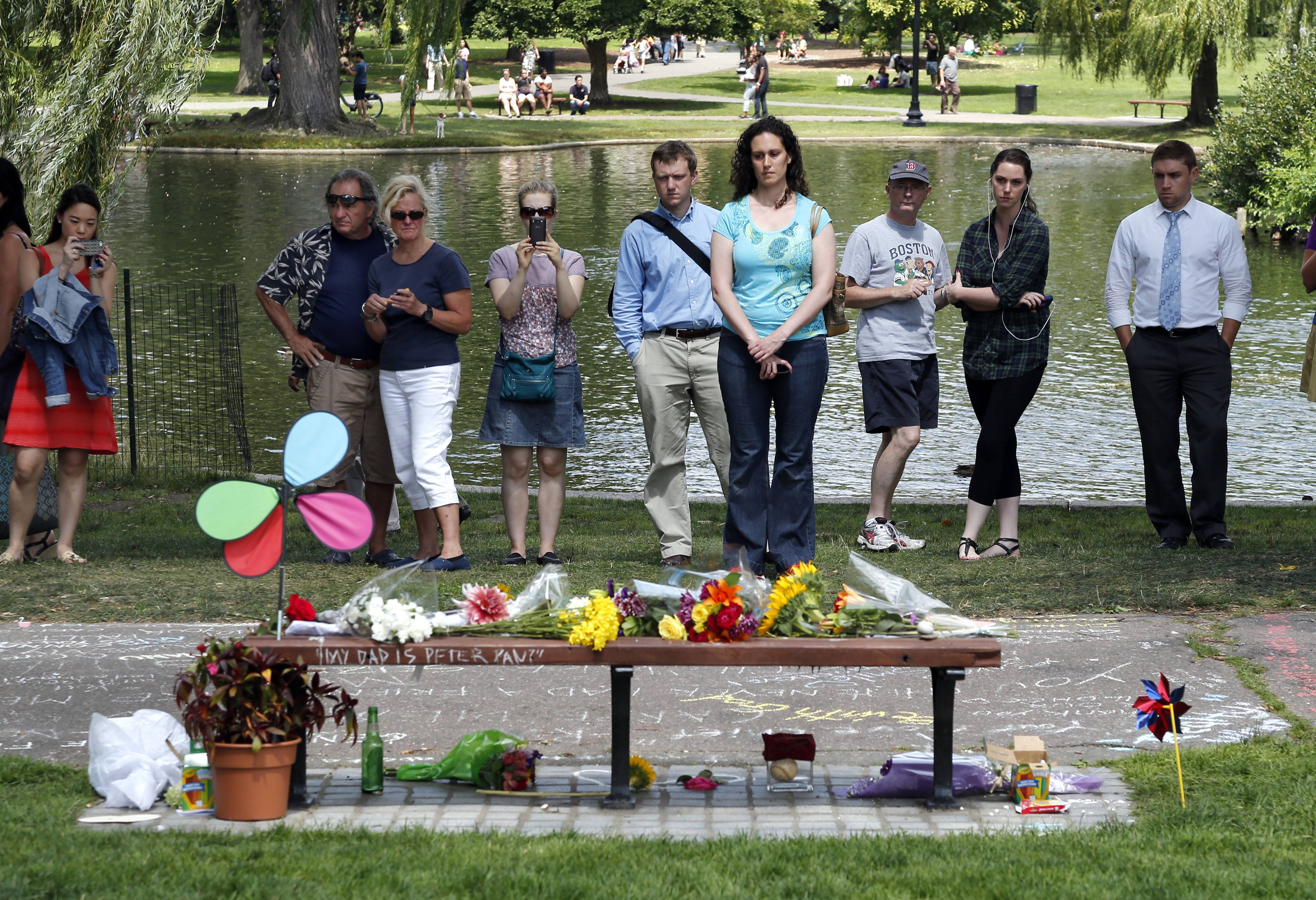 "People pause by a bench at Boston's Public Garden Tuesday, where a small memorial has sprung up at the place where Robin Williams filmed a scene during the movie, ""Good Will Hunting."""