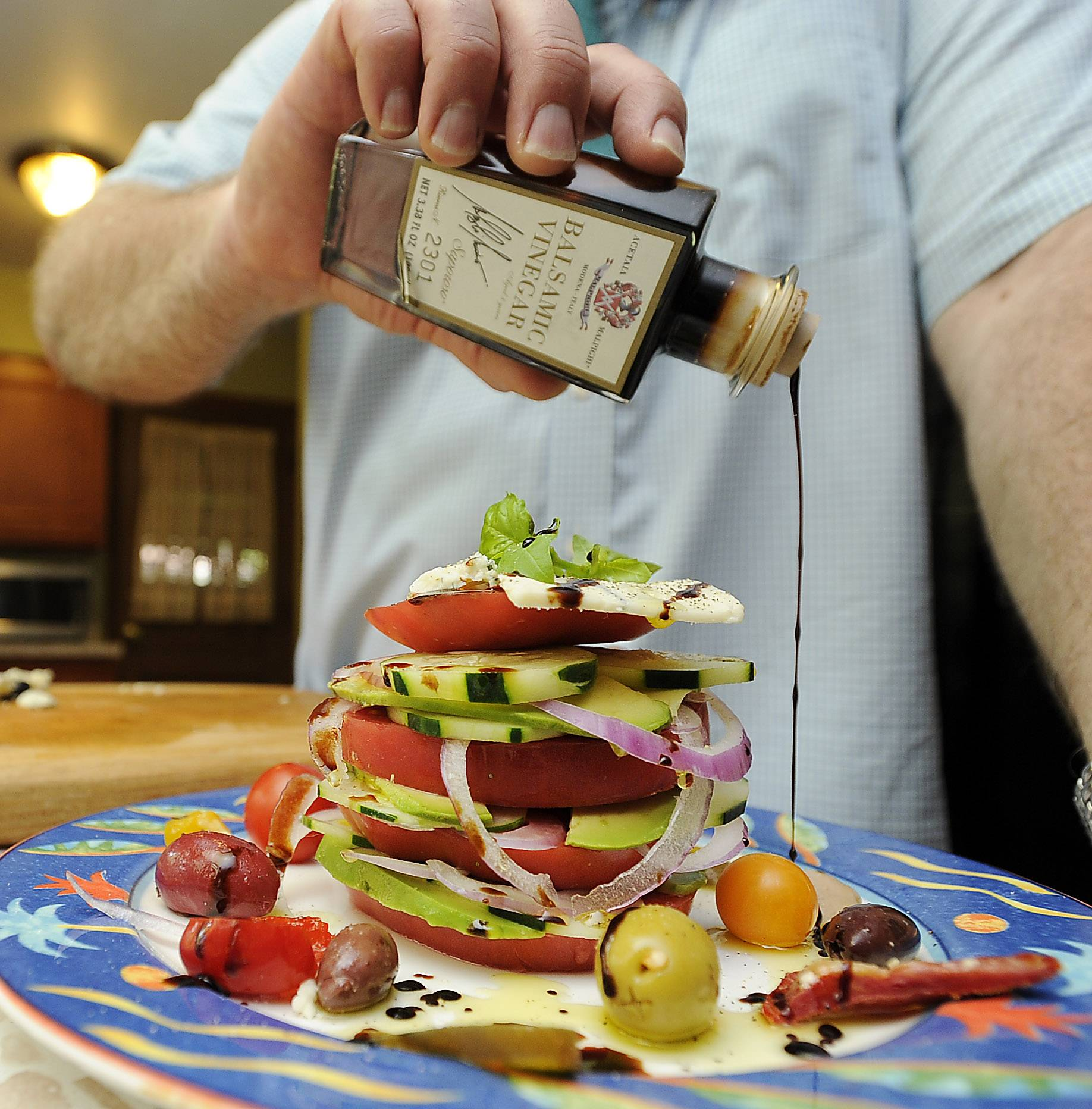 Kevin Kilgore tops off his Fat Stax Tomato Salad with balsamic vinegar.