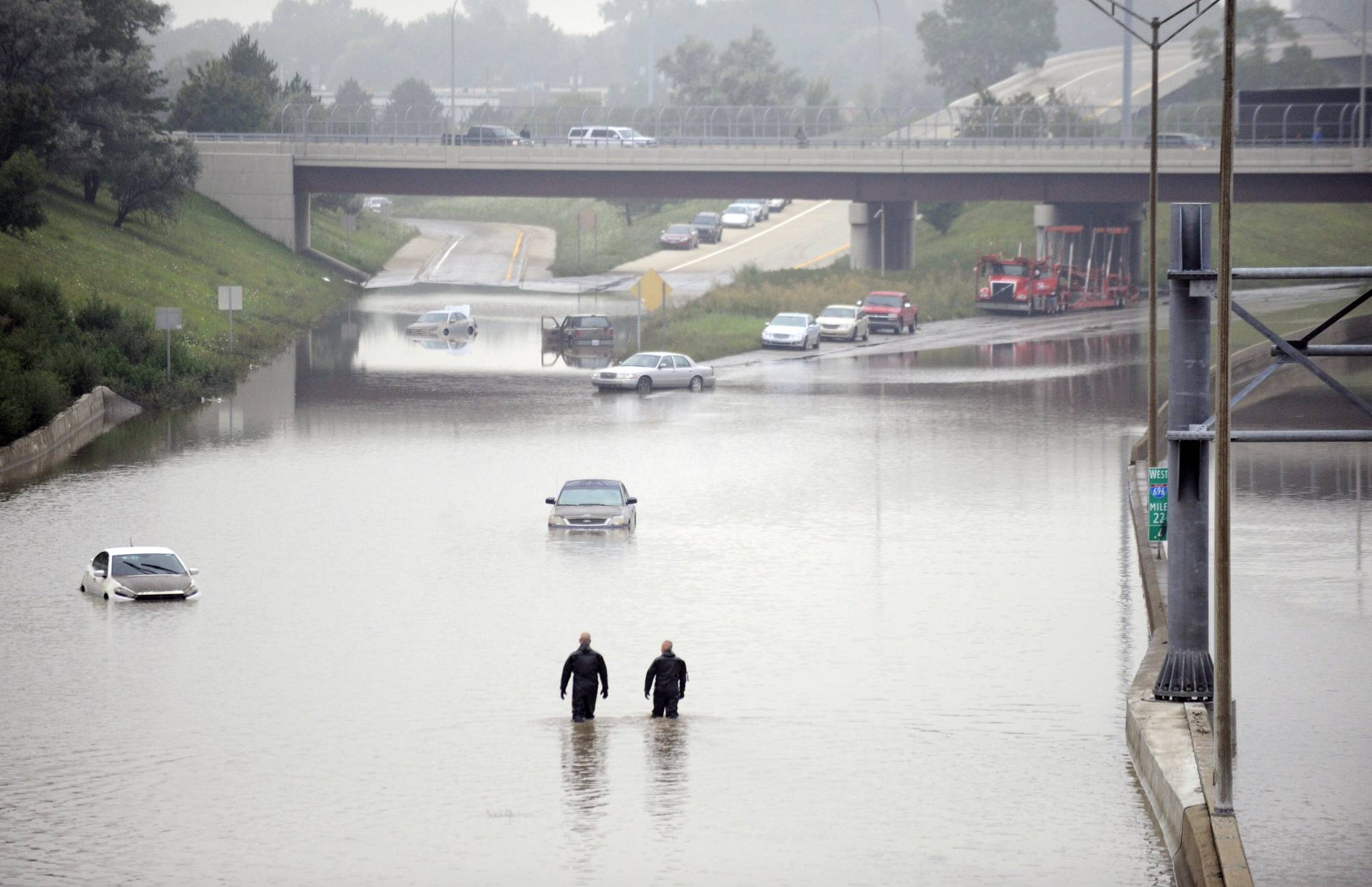 Cars are stranded along a flooded stretch of Interstate 696 at the Warren, Mich., city limits Tuesday morning, Aug. 12, 2014. Police divers are searching for anyone trapped in their vehicles.