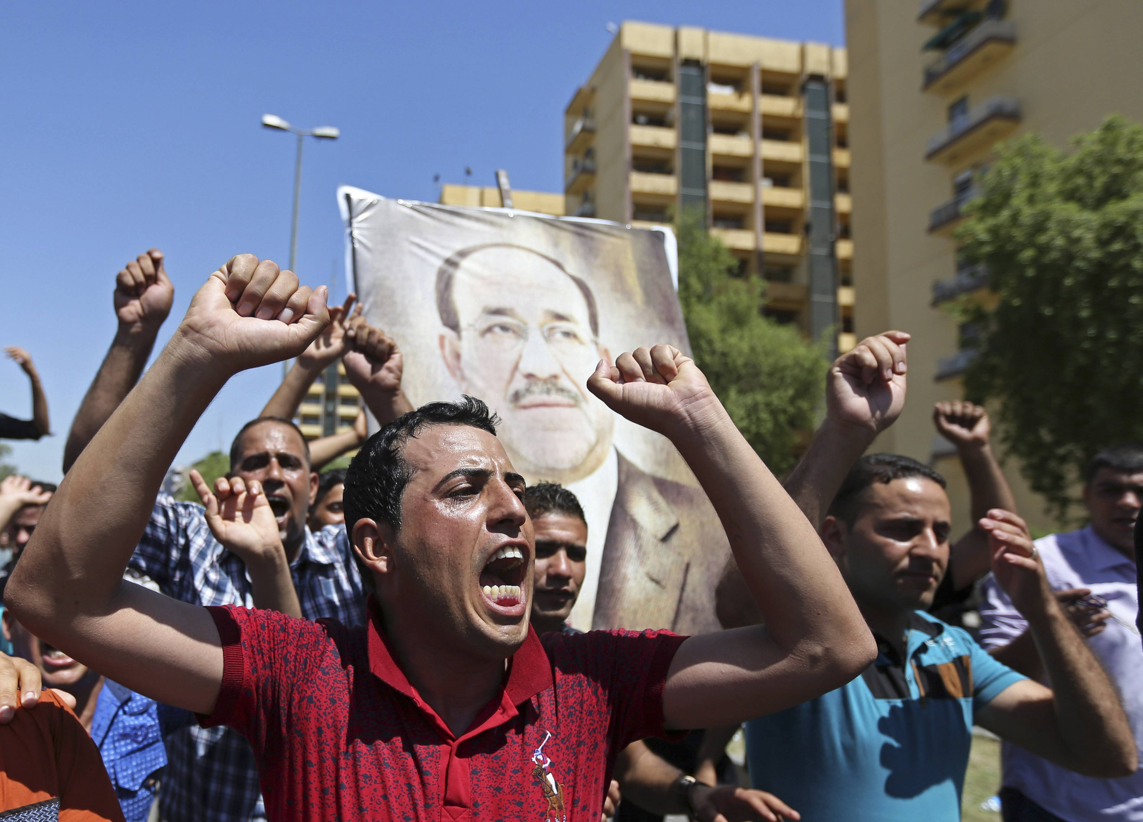 Iraqis chant pro-government slogans and display placards bearing a picture of embattled Prime Minister Nouri al-Maliki during a demonstration in Baghdad, Iraq, Monday, Aug. 11, 2014.