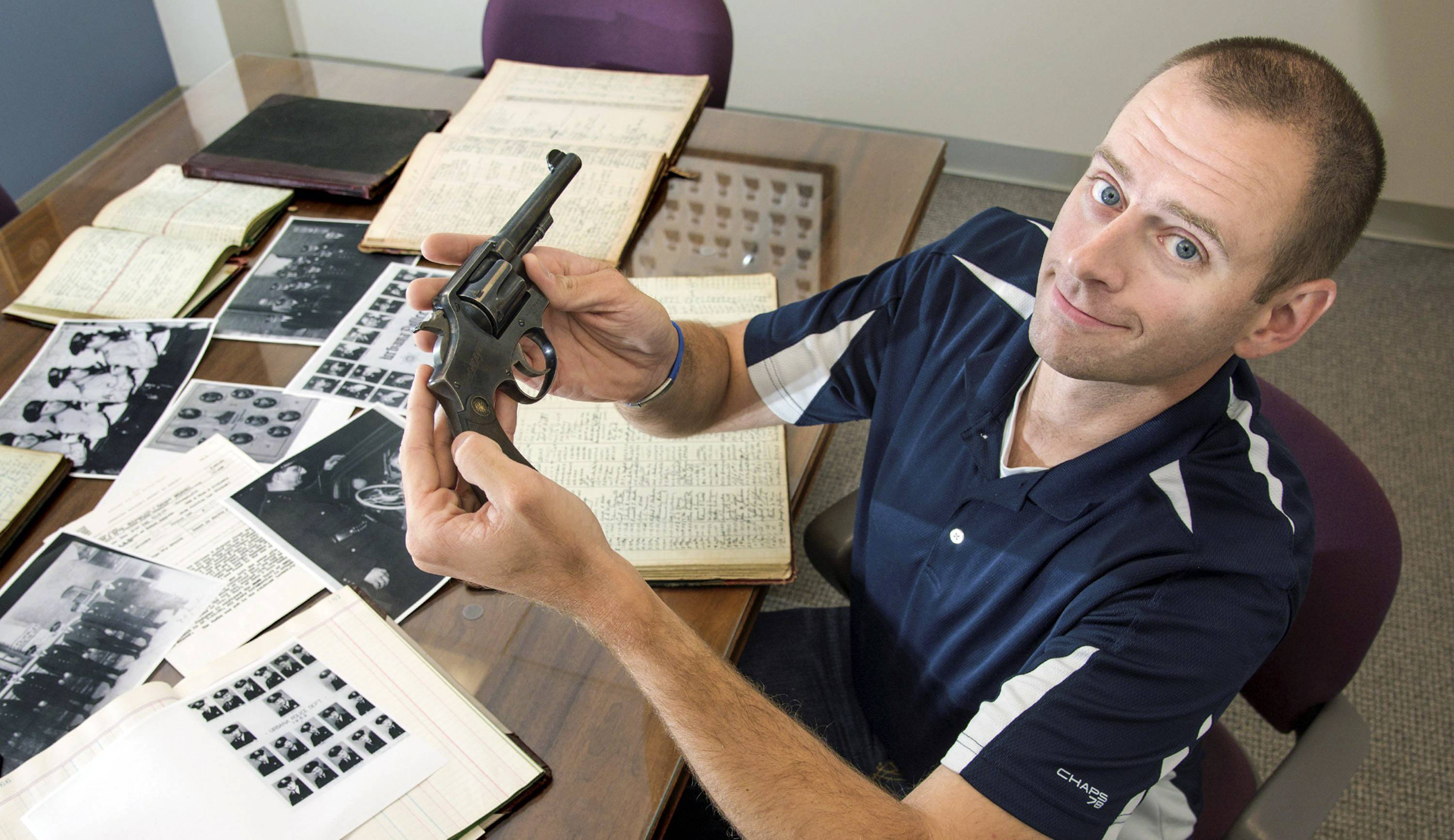 Matt Rivers, a detective with the Urbana Police Department, shows a .38 Special revolver owned by the department's police chief in 1933.