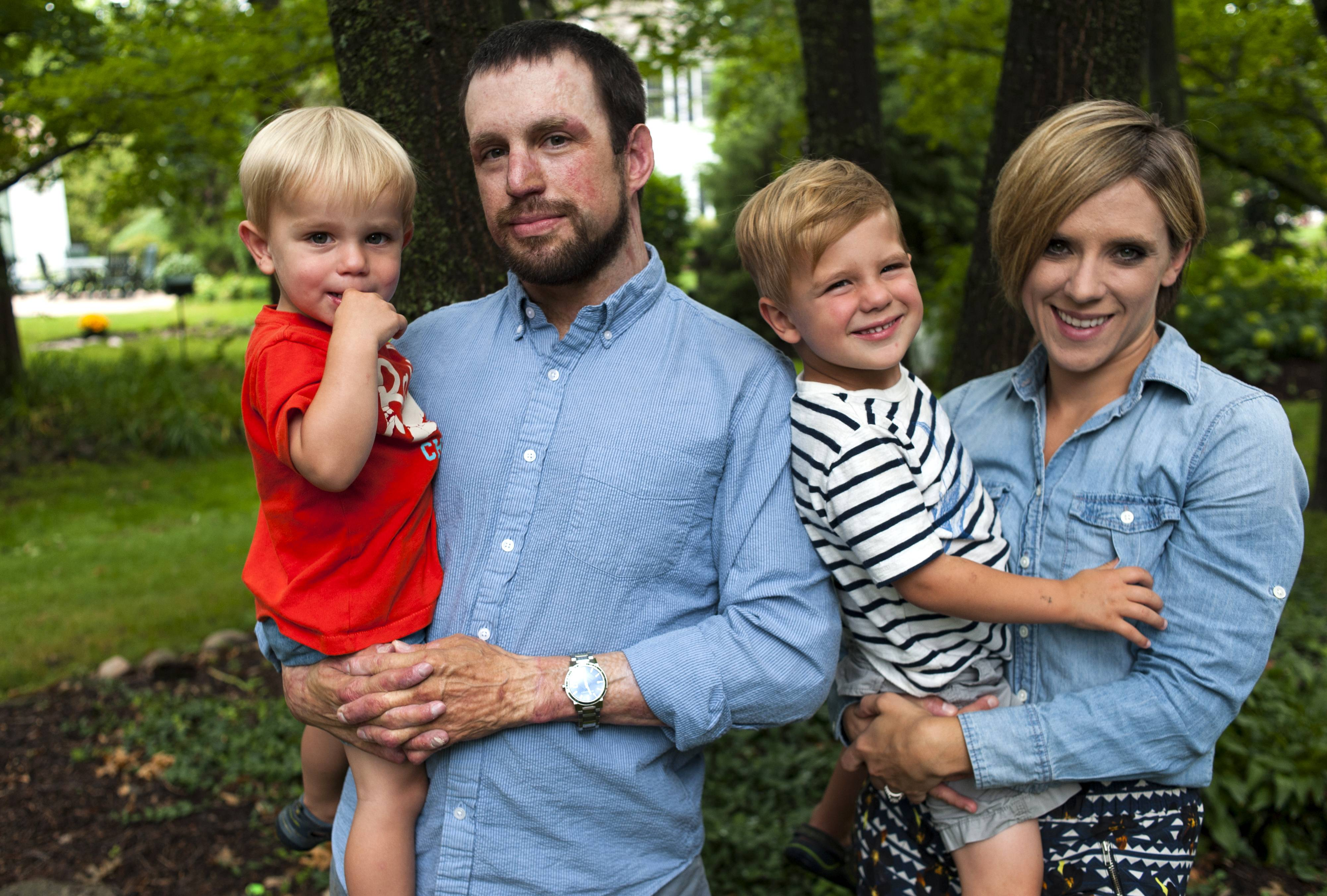 Holding sons Gavin, 2, left, and Brogan, 3, Army veterans Breg and Allison Hughes say they got support from several charities after he was wounded and burned by a roadside bomb while serving in Afghanistan in 2012.