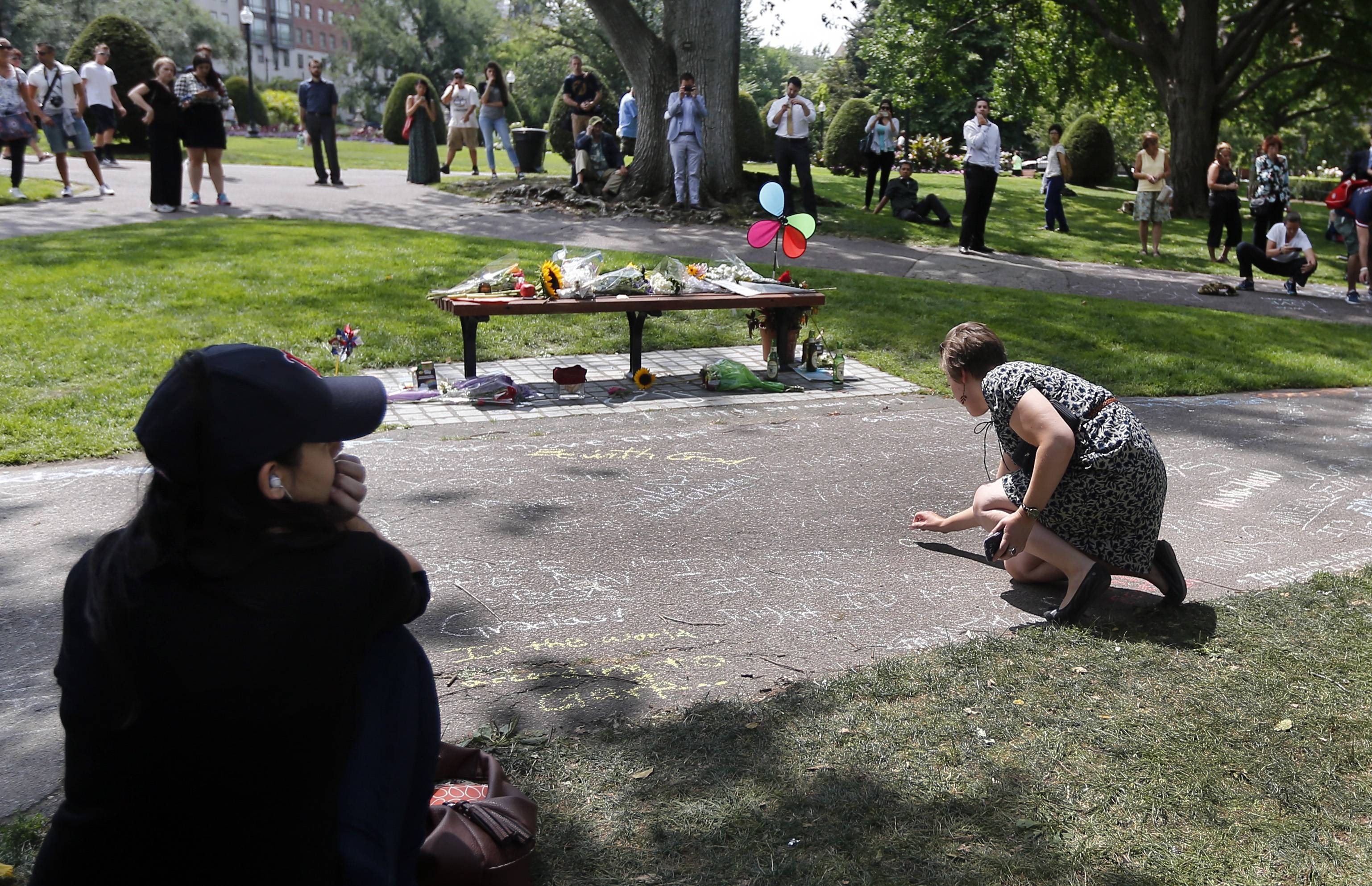 "A women writes a message with chalk as others gather near a bench at Boston's Public Garden Tuesday, where a small memorial has sprung up at the place where Robin Williams filmed a scene during the movie, ""Good Will Hunting."""