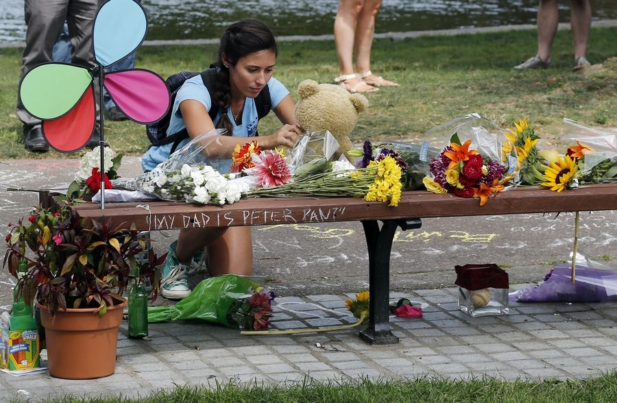 "Mariagrazia LaFauci, 24, of Waltham, Mass. places a teddy bear on a bench at Boston's Public Garden Tuesday, where a small memorial has sprung up at the place where Robin Williams filmed a scene during the movie, ""Good Will Hunting."""