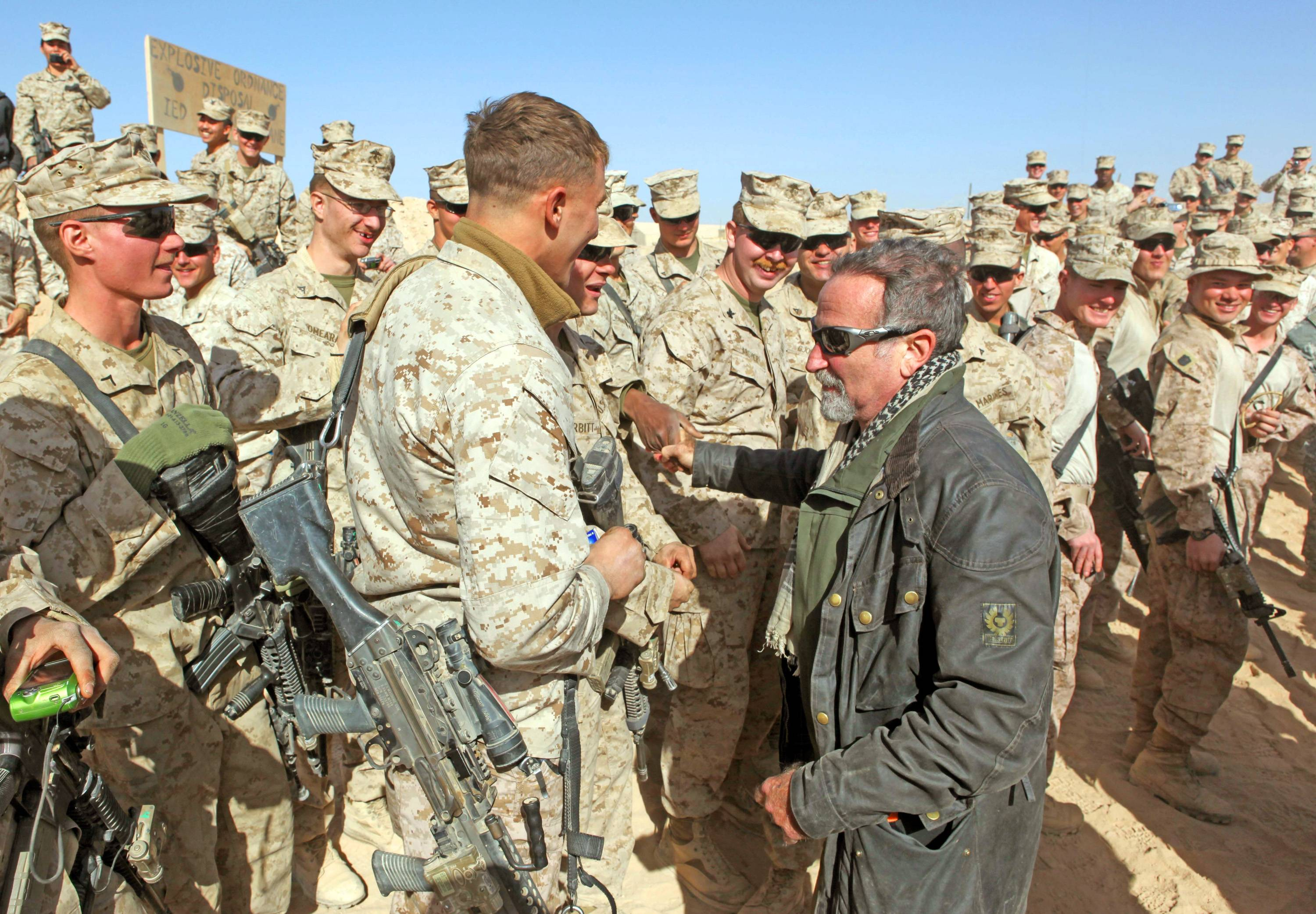 Actor-comedian Robin Williams shakes hands with Marines from 2nd Battalion, 9th Marine Regiment, during the USO's Holiday Troop Visit tour that stopped at Camp Hanson in Marjah, Helmand province, Afghanistan.