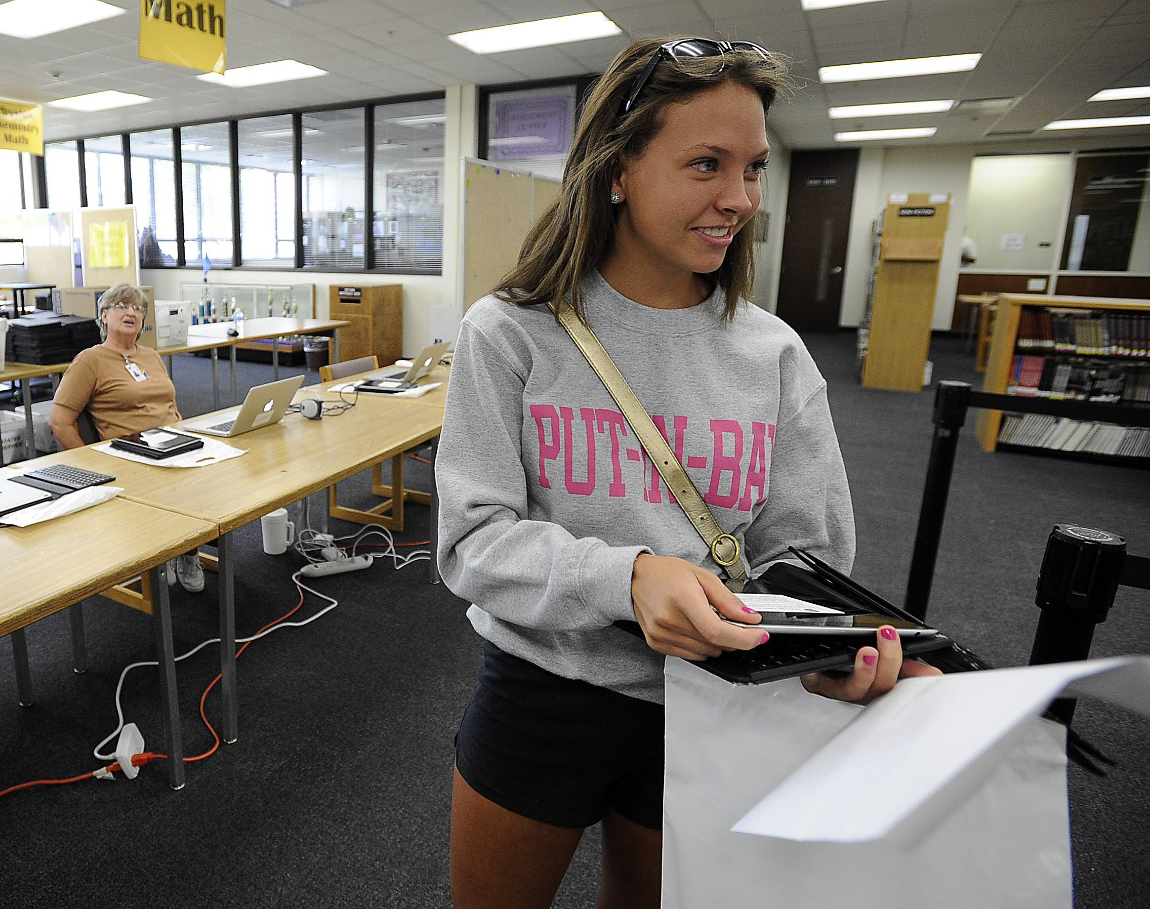 Macy Serna, 17, of Arlington Heights picks up her new iPad at Rolling Meadows High School. Dist. 214 has been incorporating more and more iPad usage in the classroom, eventually leading to every student having a device that they keep year-round.
