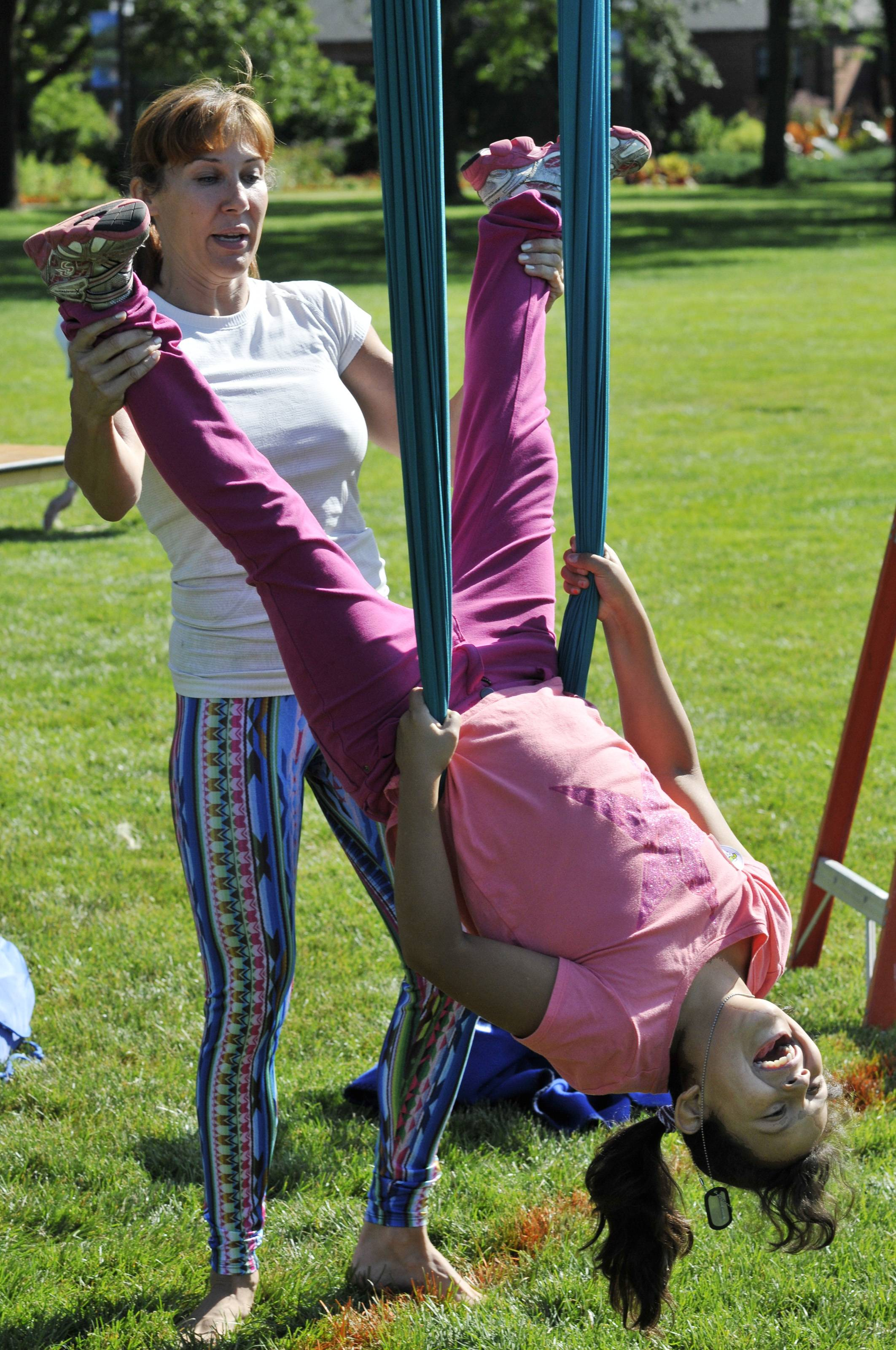 Rebeca Riser, owner of Flying Buddha Fitness in Wheaton, shows Jayden Huesca of West Chicago how to do an aerial yoga move during a Kids' Fitness and Health Boot Camp Friday at Cantigny Park.