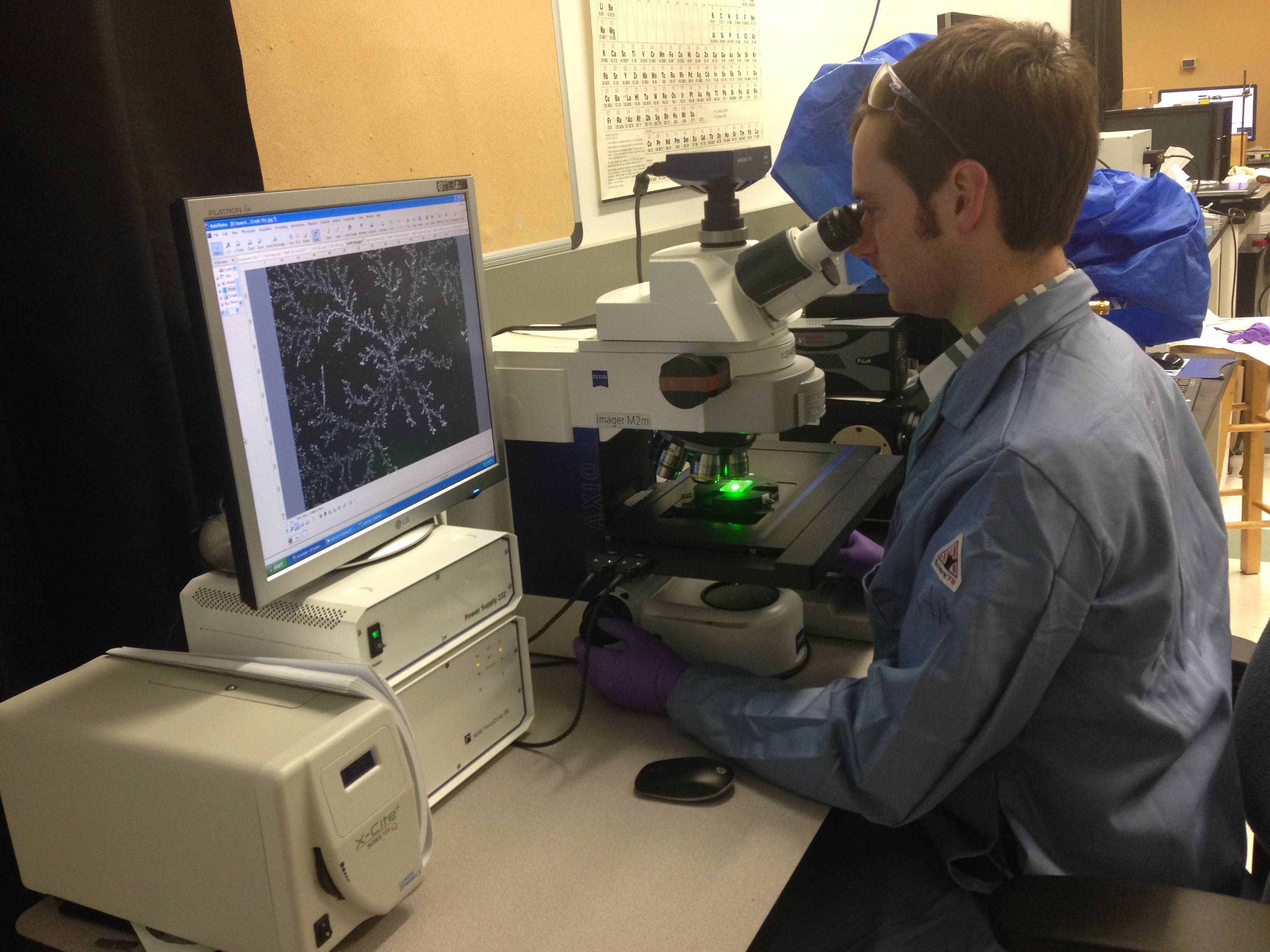 Dr. Keith Brown uses an optical microscope to examine the salt crystal seen on the monitor. The optical microscope uses a system of lenses and light to magnify very tiny things so they can be inspected closely.