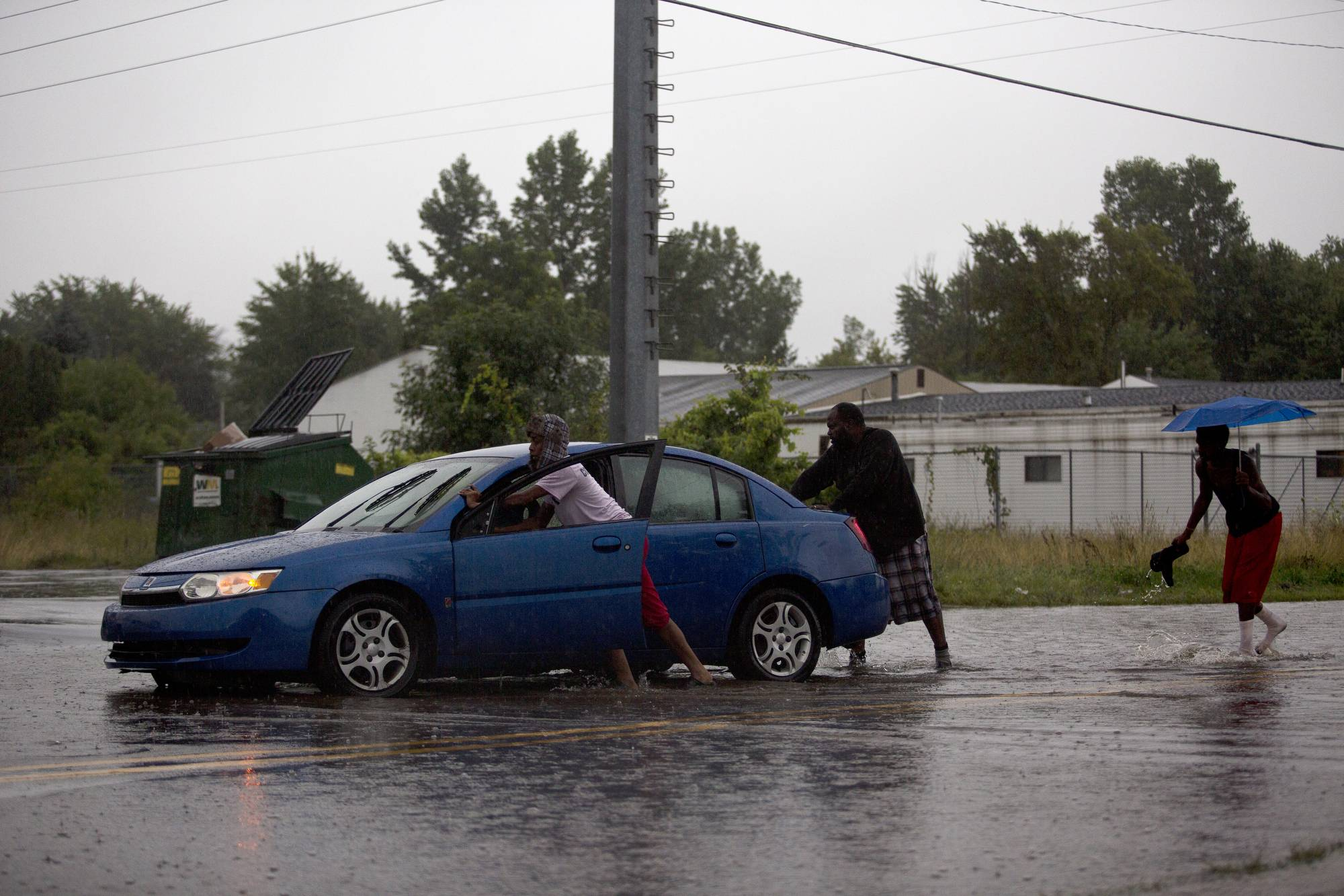 Flint resident Brittany Thomas gets help from friends after getting stuck on Lavelle Rd. just south of Pasadena Ave. in Flint, Mich. after a storm produced heavy rain and flooding.
