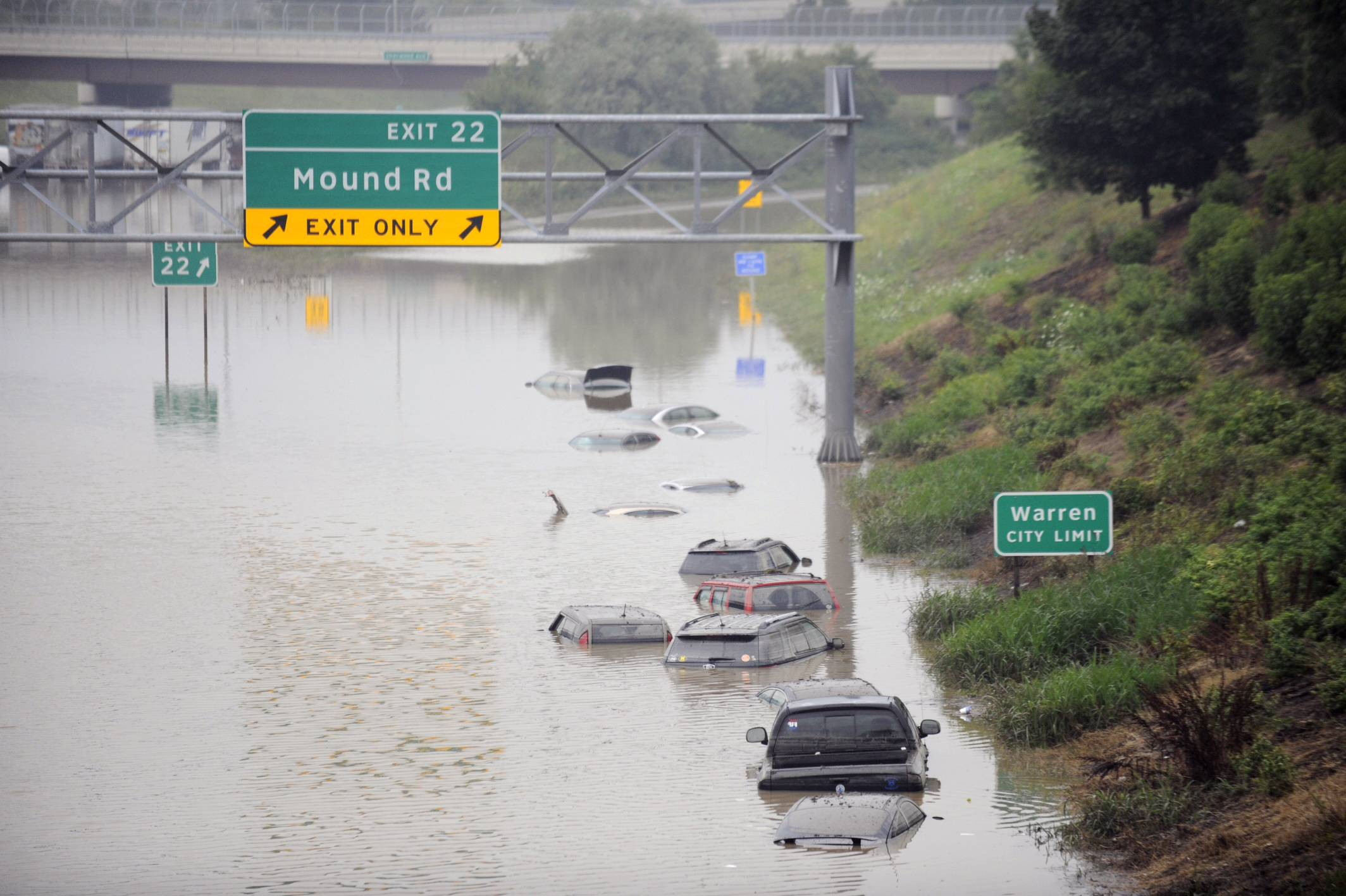Cars are stranded along a flooded stretch of I-696 at the Warren, Mich. city limits Tuesday morning, Aug. 12, 2014. Warren Mayor James Fouts said roughly 1,000 vehicles had been abandoned in floodwaters in the suburb where many roads were closed after 5.2 inches of rain fell Monday.