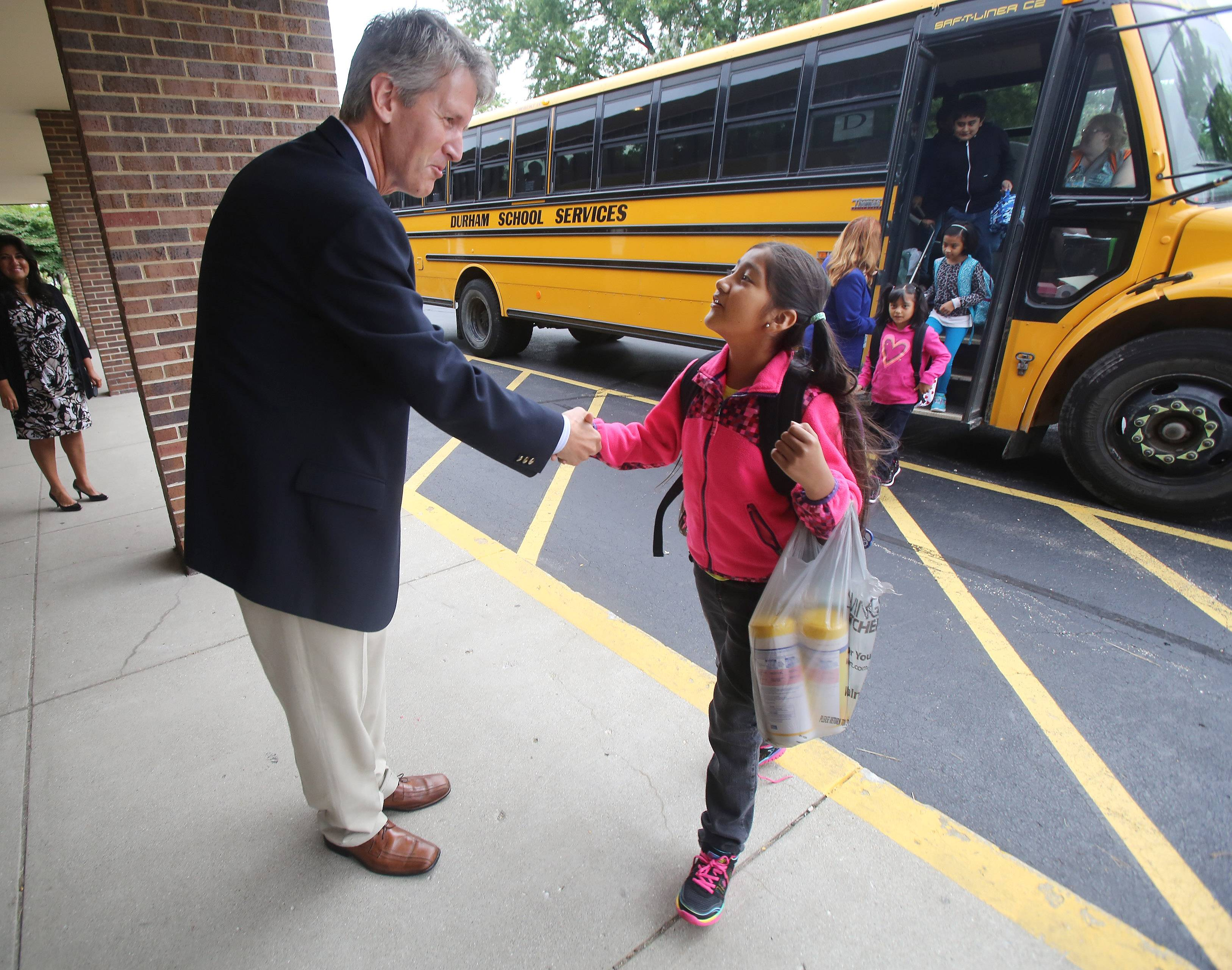 Mundelein Elementary District 75's new superintendent, Andy Henrikson, shakes hands with Giselle Hernandez as she exits the bus for the first day of classes at Mechanics Grove School in Mundelein. Henrickson and Principal Kathleen Miller greeted students Tuesday.