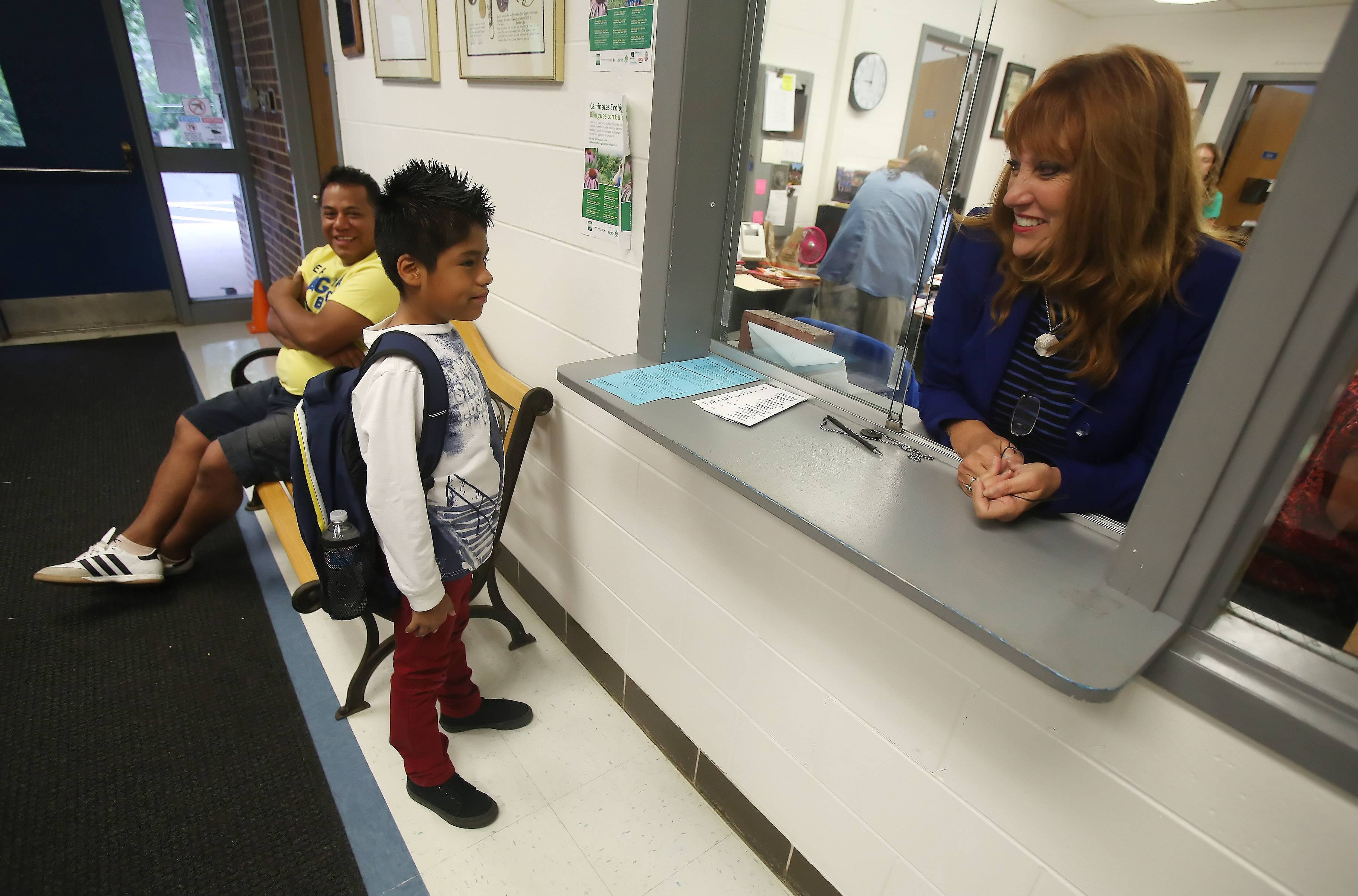 Mechanics Grove Elementary School Principal Kathleen Miller talks with fourth-grader Brandon Jimenez, as his father, Antonio, drops him off for the first day of classes in Mundelein on Tuesday. Miller and Mundelein Elementary District 75's new superintendent, Andy Henrickson, greeted students when they arrived.