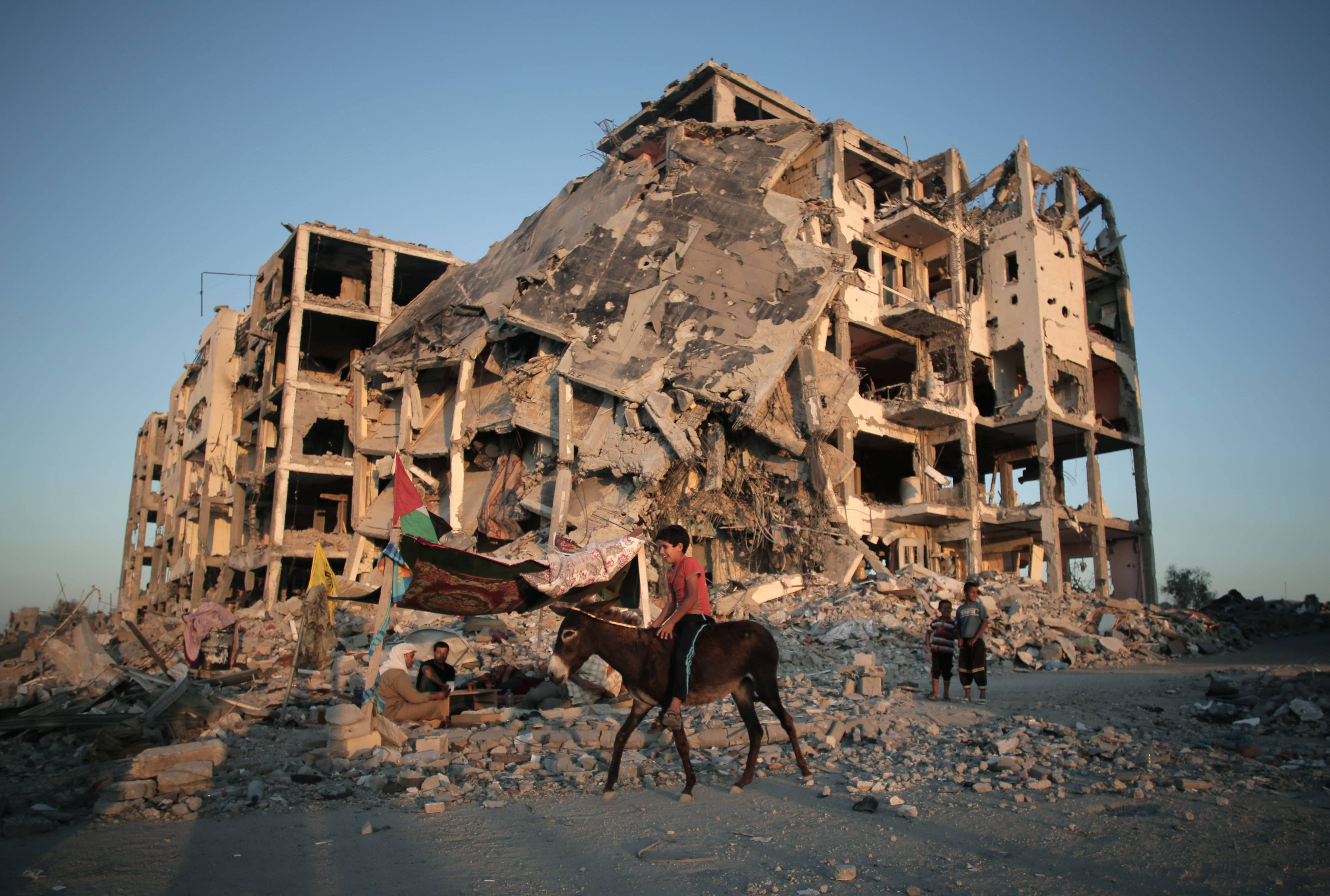 A Palestinian boy rides a donkey next to the destroyed Nada Towers residential neighborhood in the town of Beit Lahiya, northern Gaza Strip, Monday, Aug. 11, 2014.