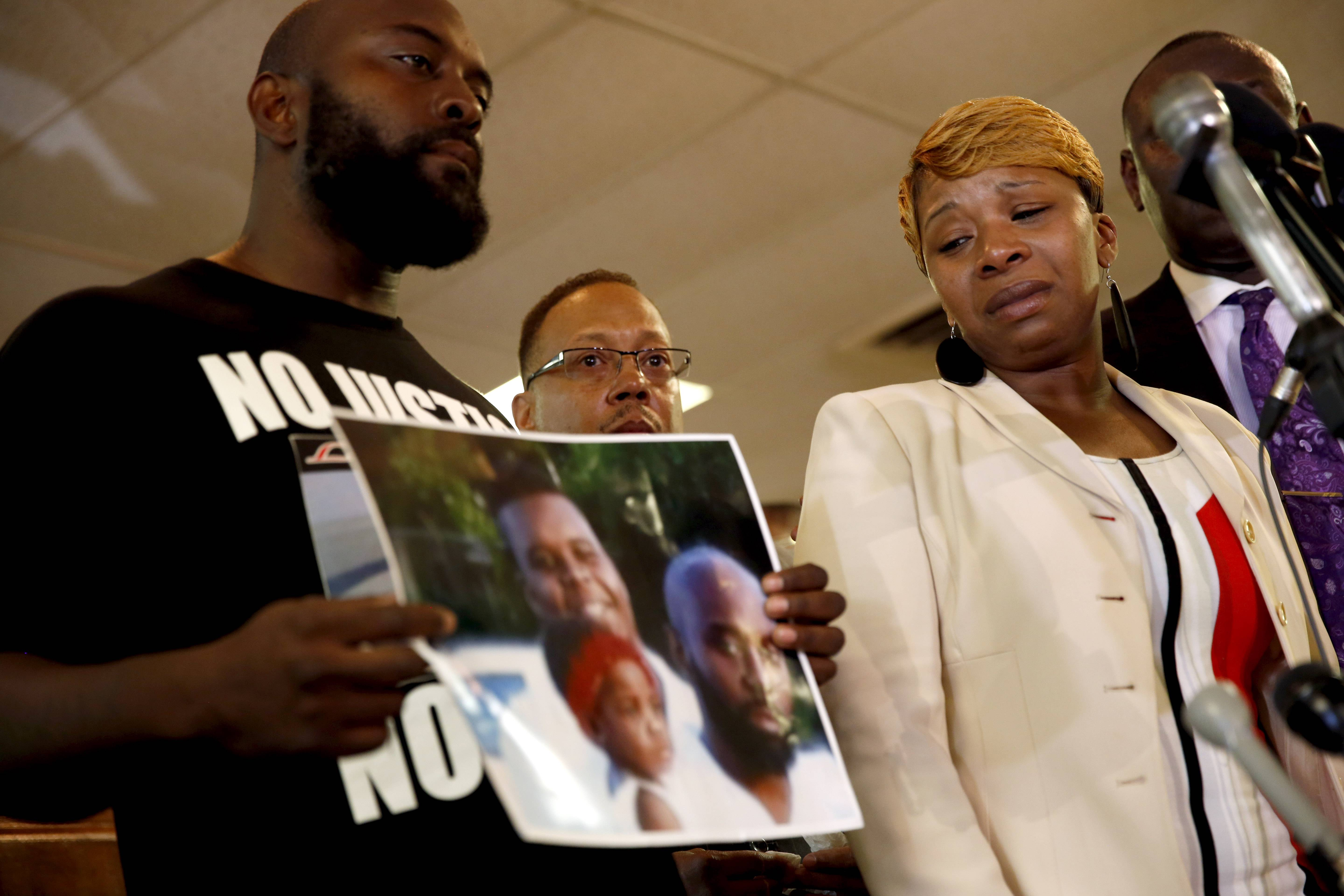 Lesley McSpadden, right, the mother of 18-year-old Michael Brown, watches as Brown's father, Michael Brown Sr., holds up a family picture of himself, his son, top left in photo, and a young child during a news conference Monday, Aug. 11, 2014, in Ferguson, Mo. Michael Brown, 18, was shot and killed in a confrontation with police in the St. Louis suburb of Ferguson, Mo, on Saturday, Aug. 9, 2014.