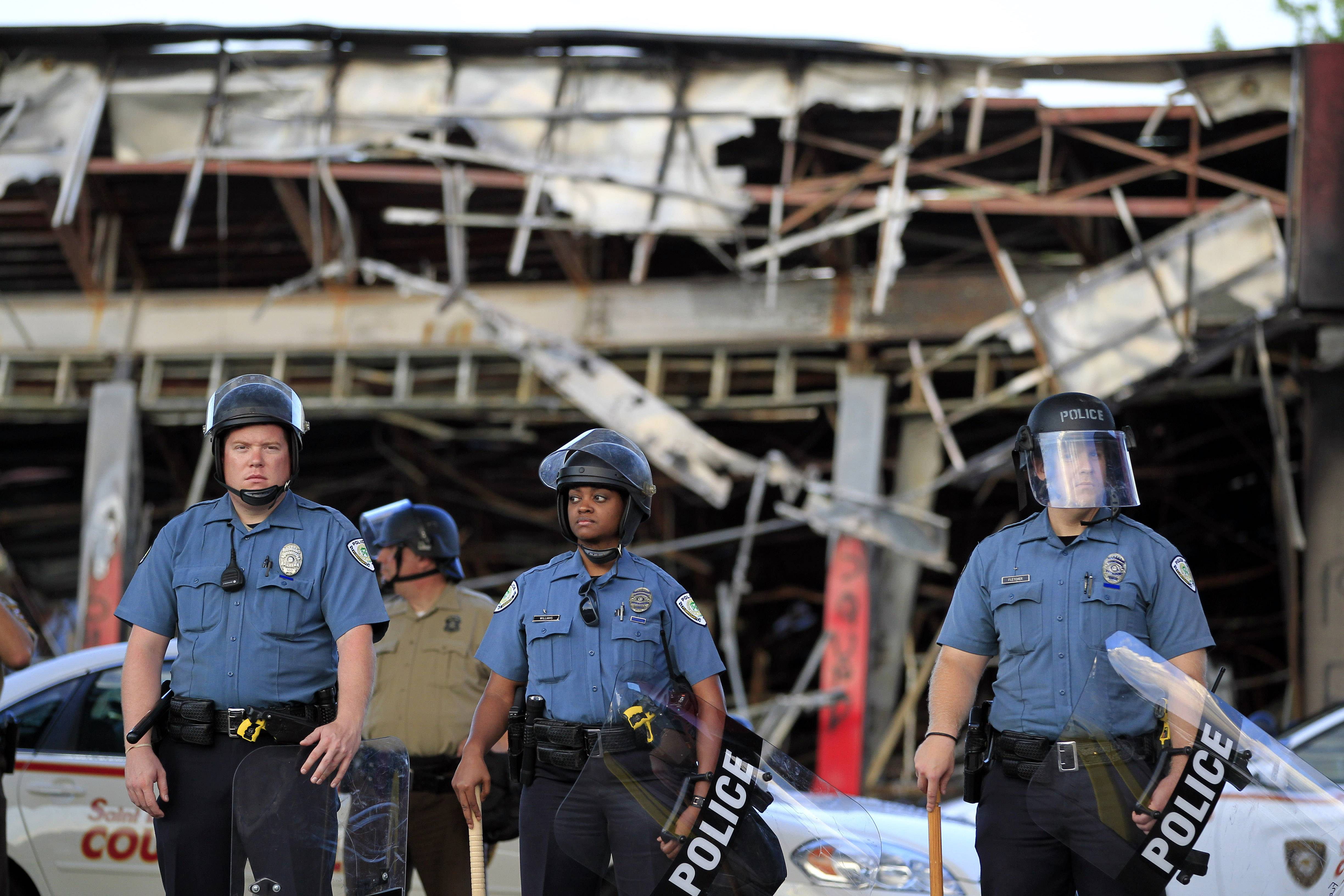 Police wearing riot gear stage outside the remains of a burned out convenience store Monday in Ferguson, Mo. Authorities in Ferguson used tear gas and rubber bullets to try to disperse a large crowd Monday night that had gathered at the site of a burned-out convenience store damaged a night earlier, when many businesses in the area were looted.