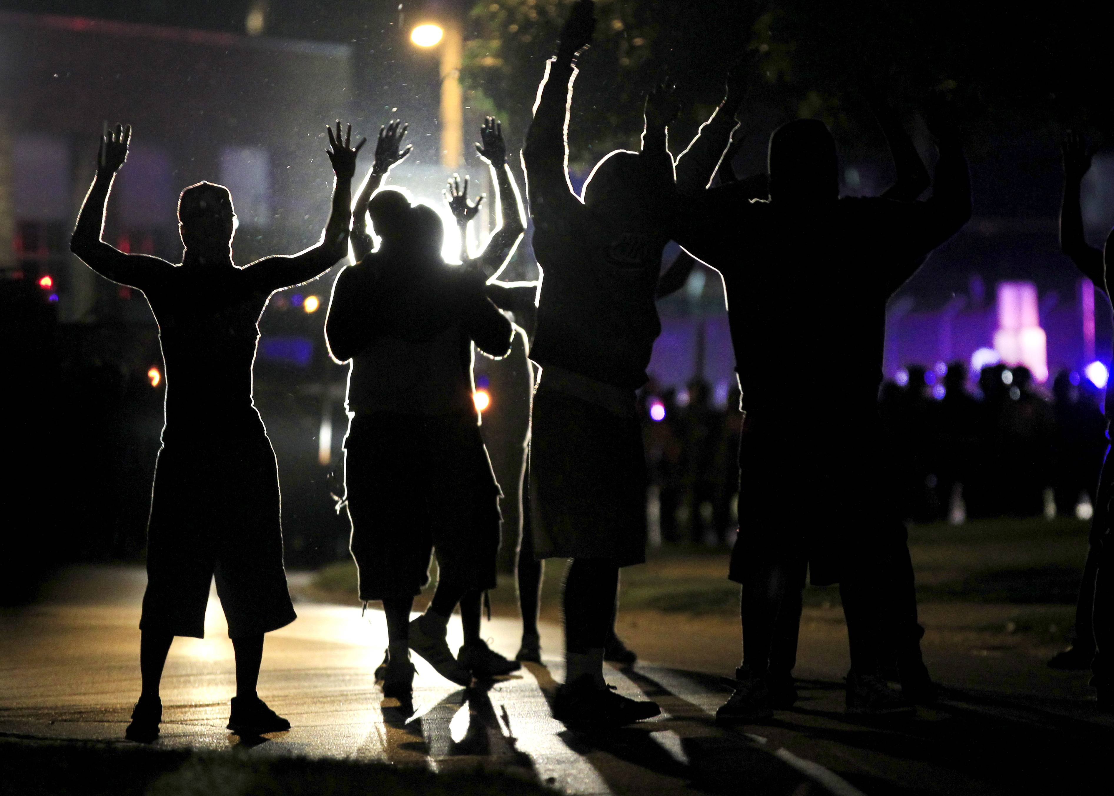People raise their hands in the middle of the street as police wearing riot gear move toward their position trying to get them to disperse Monday in Ferguson, Mo. The FBI opened an investigation Monday into the death of 18-year-old Michael Brown, who police said was shot multiple times Saturday after being confronted by an officer in Ferguson.