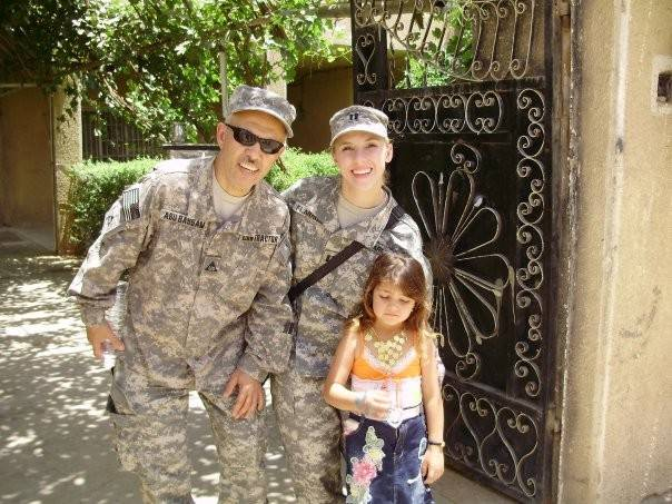 A helicopter pilot during his first tour of duty in Iraq, Army Capt. Allison Hughes, center, poses with her interpreter and a neighborhood girl during her second tour in Baghdad coordinating air support for the troops. She now runs a charity out of her Barrington home to support caregivers of wounded soldiers.