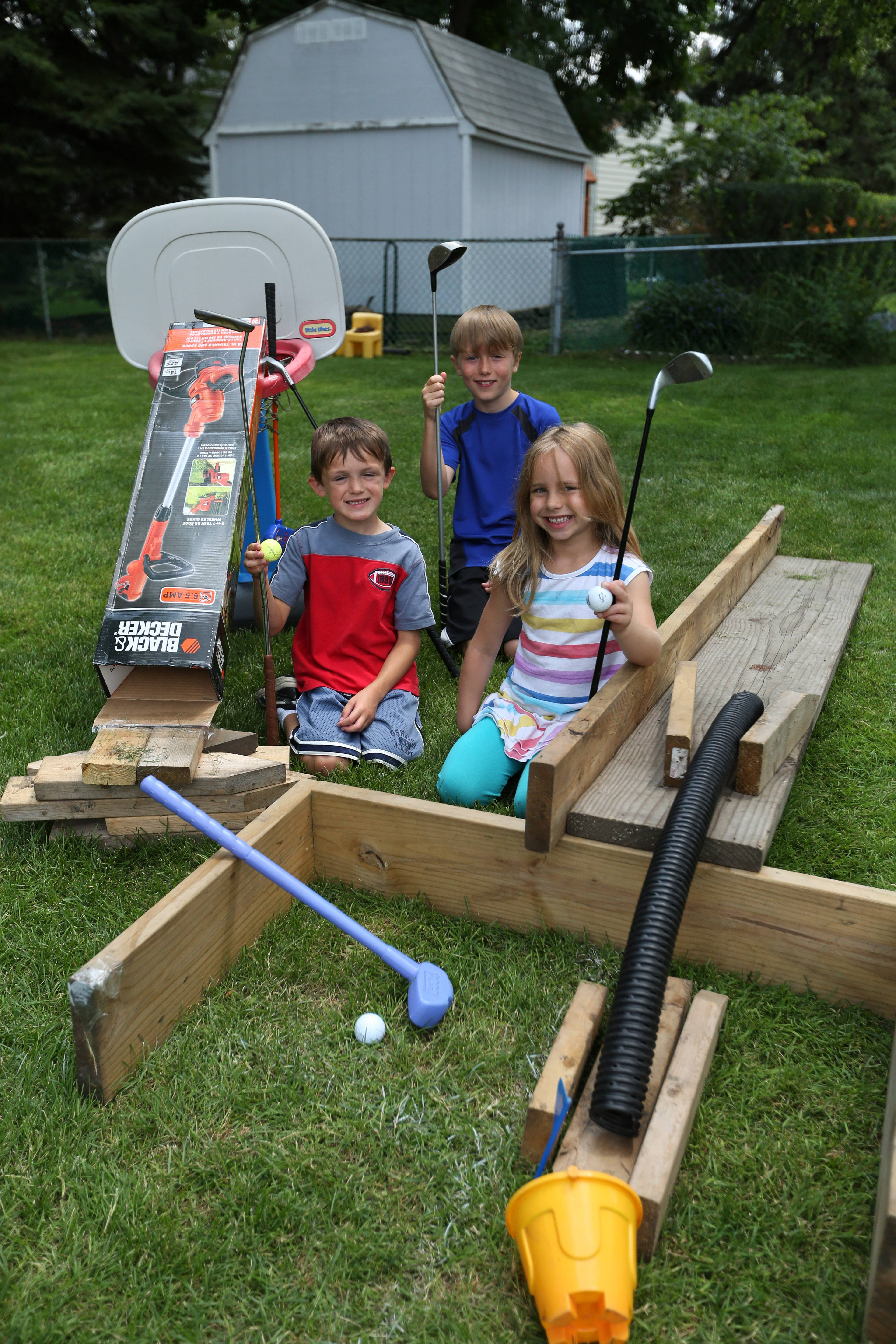 Rylan Williams, 9, background, his brother Caden, 5, left, and friend Lily Anderson, 6, created a homemade mini golf course made out of boards, a basketball hoop, tubes, buckets, and other items.