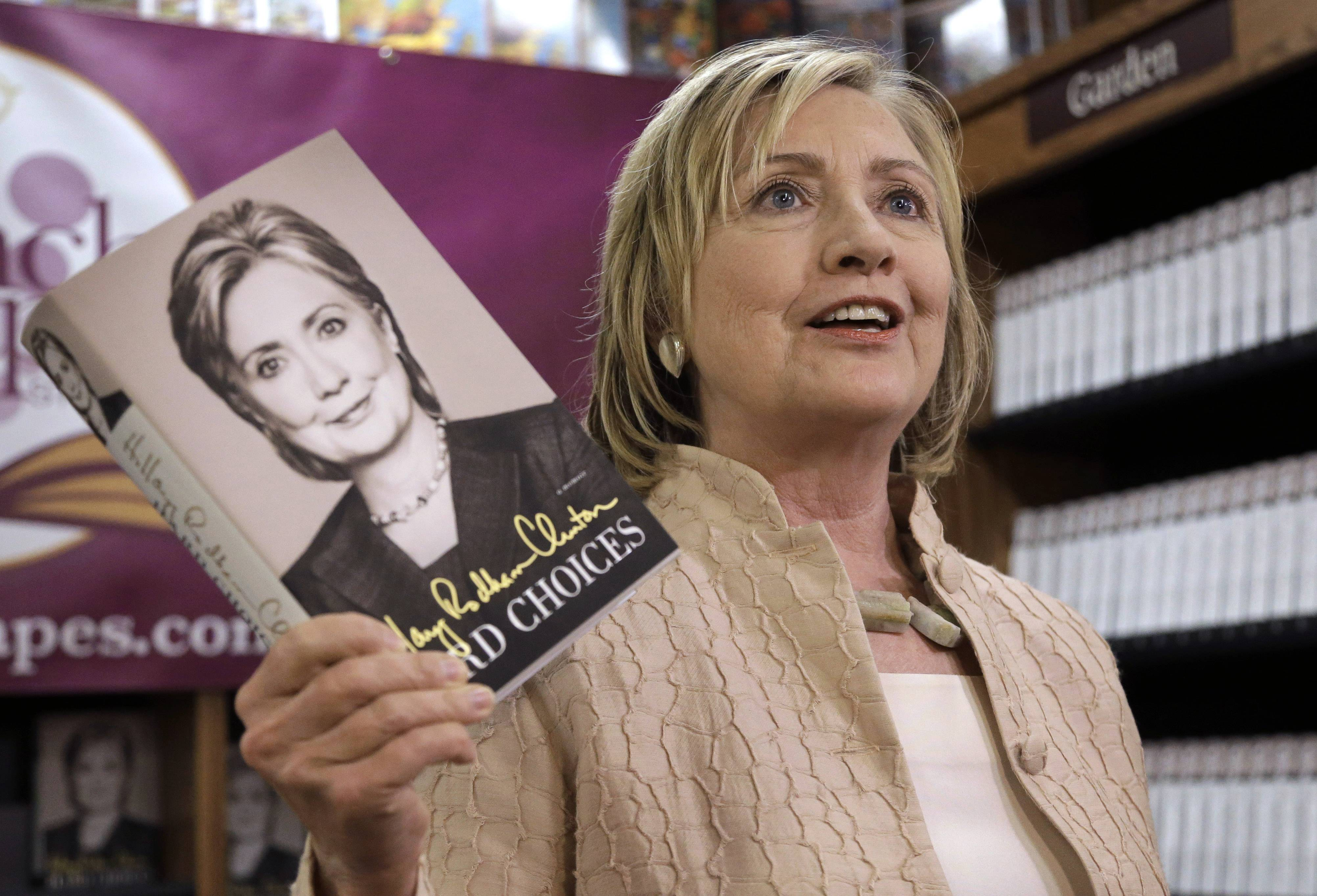 "Former Secretary of State Hillary Rodham Clinton holds her memoir ""Hard Choices"" at a bookstore in Vineyard Haven, Mass., on the island of Martha's Vineyard, Wednesday, during a book signing event."