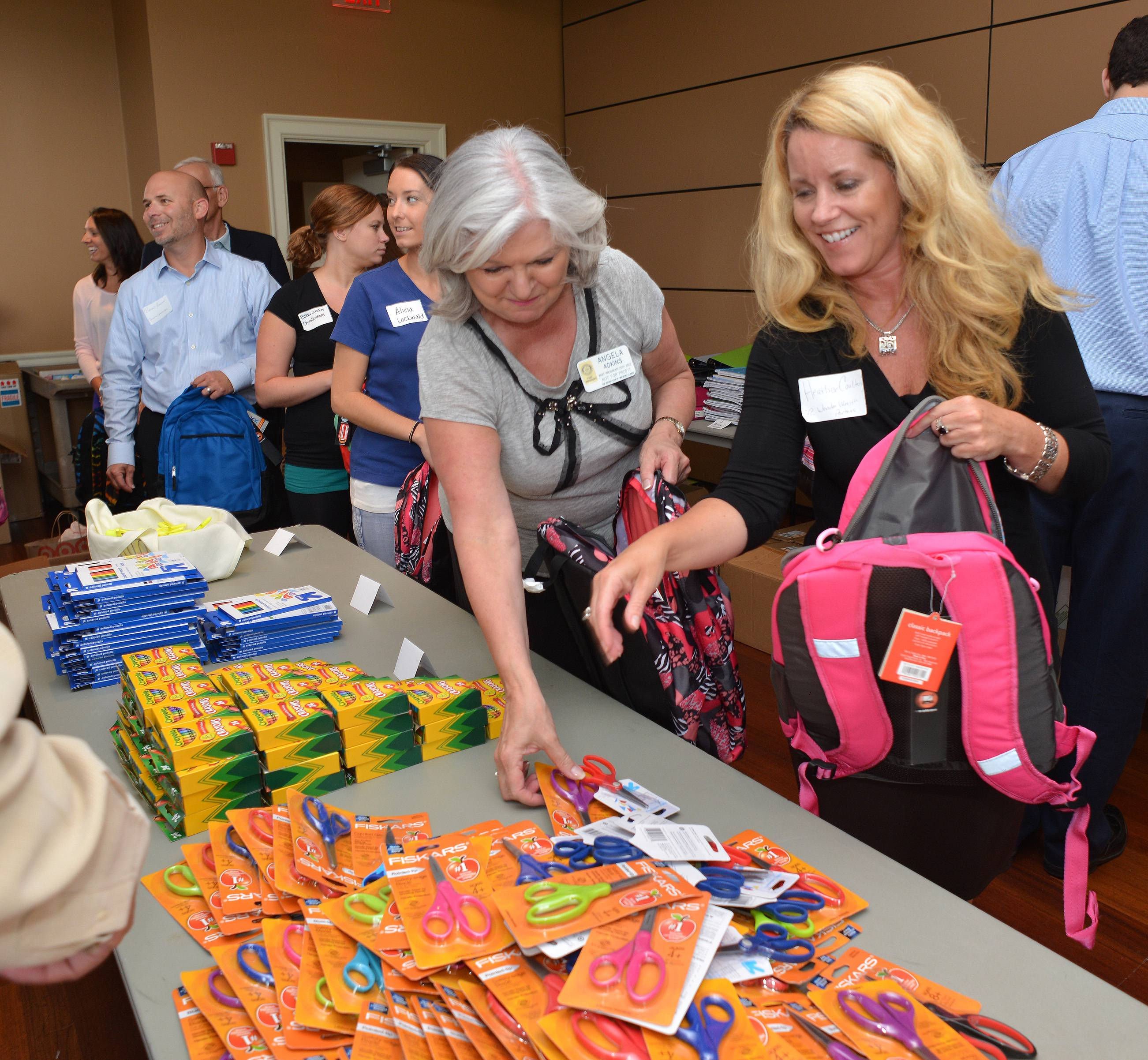 Wheaton Rotary Club and Wheaton Chamber of Commerce members filled more than 150 donated backpacks for kids in need Wednesday following a luncheon at Arrowhead Country Club in Wheaton. Angela Adkins, second right, and Heather Coulter, right, grab donated supplies for their backpacks.