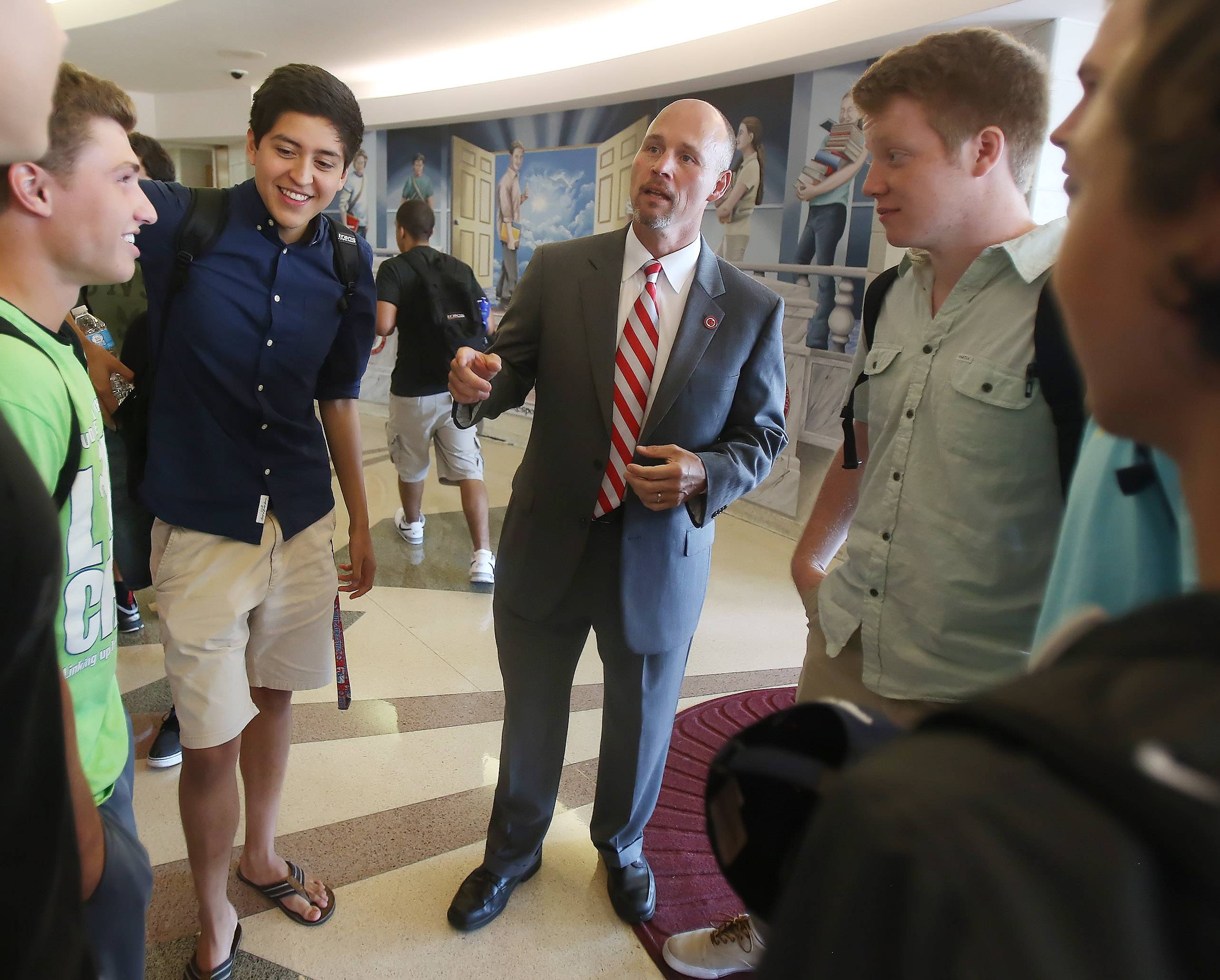 Mundelein High School District 120's new superintendent, Kevin Myers, talks to a group of students on the first day of school. Mundelein High School is giving each student a Chromebook laptop to work with this year as part of a new program.