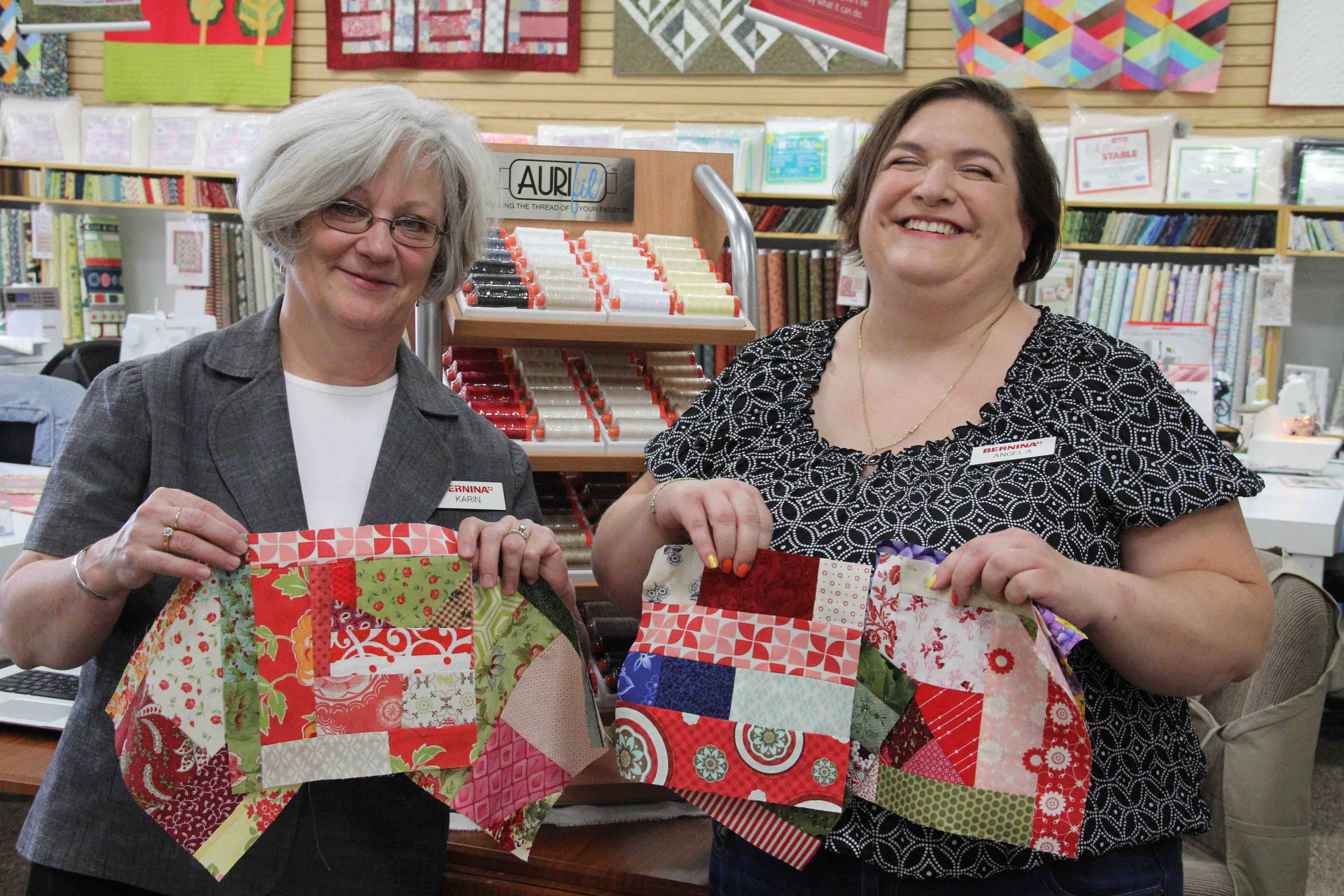 Owner Karin Furio and Angela Aldaz display quilt blocks made by volunteers at Sew Generously.