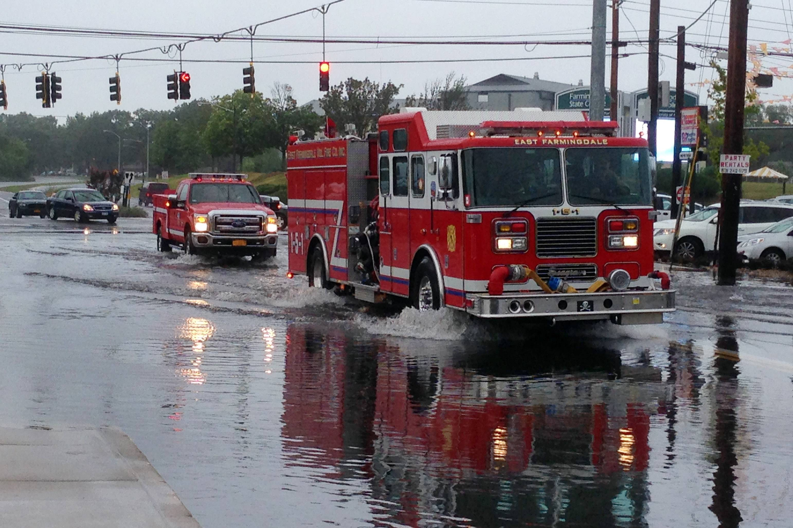 Firefighters cross a flooded intersection on Route 110 in Farmingdale, N.Y., on New York's Long Island, Wednesday, Aug. 13, 2014. Stranded Long Island drivers have been rescued after a storm slammed Islip, N.Y., with over 12 inches of rain — an entire summer's worth.