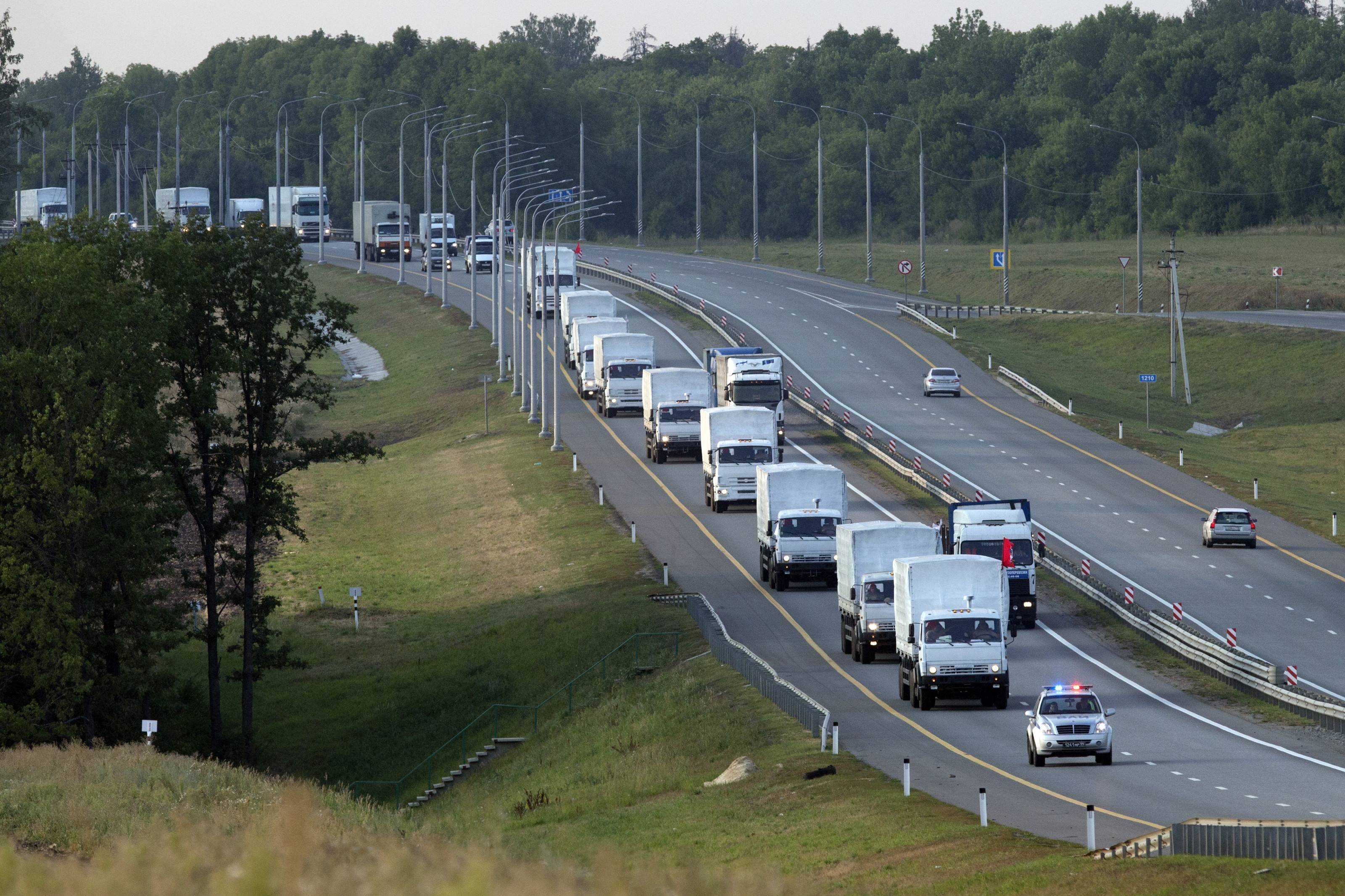 A convoy of white trucks carrying humanitarian aid passes along the main road M4 (Don highway) Voronezh region, Russia, Tuesday. The Russian trucks carrying aid intended for rebel-held eastern Ukraine were parked Wednesday in the southern city of Voronezh as doubts grew over the convoy's final route.