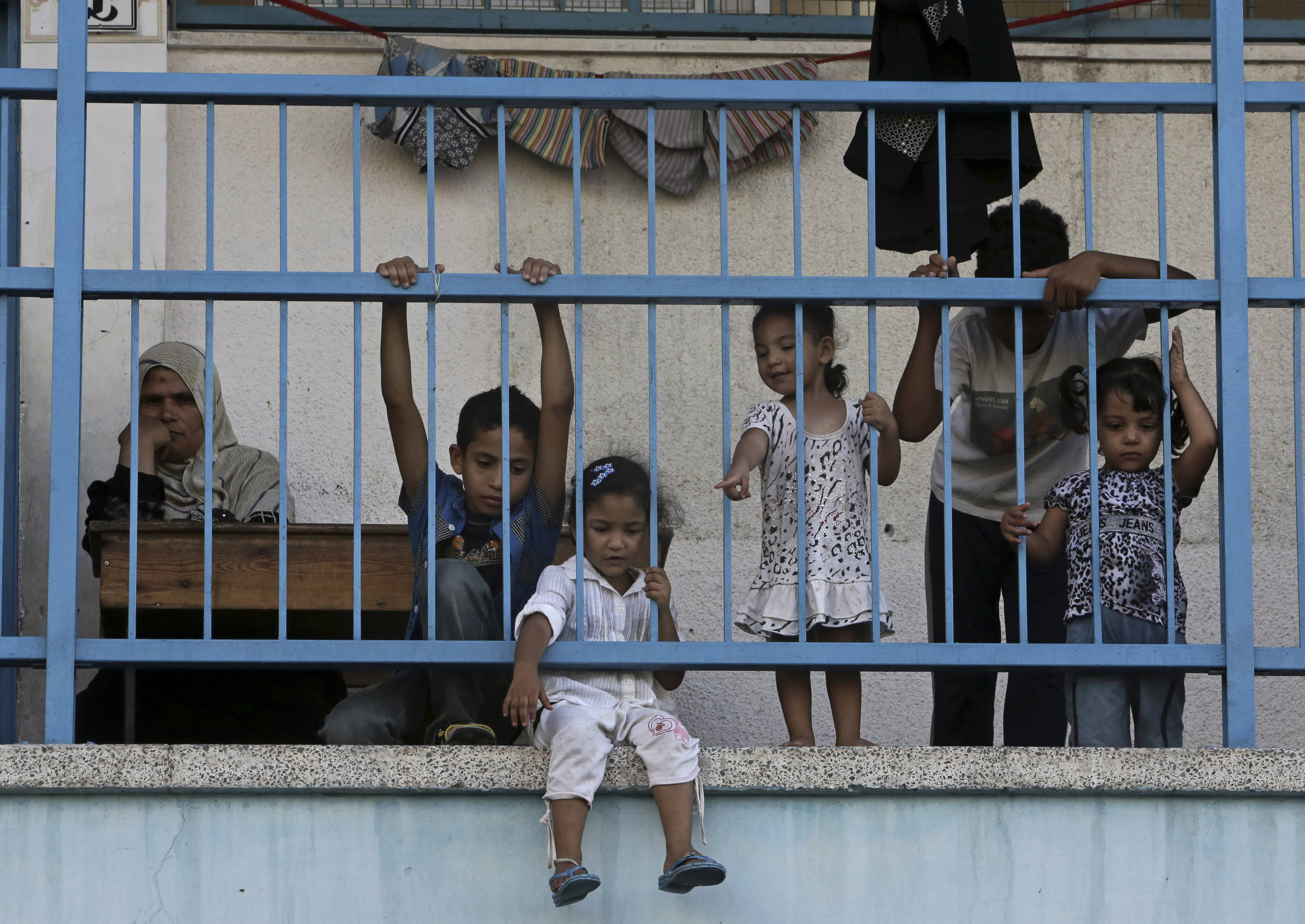 Displaced Palestinian children play on the balcony of the U.N. school where their family sought refuge during the war, in Beit Lahiya, in the northern Gaza Strip, Tuesday. Tens of thousands of Palestinians have been displaced in the Israel-Hamas war that began July 8, at least 10,000 housing units have been destroyed and many have found refuge at U.N. schools turned into shelters.