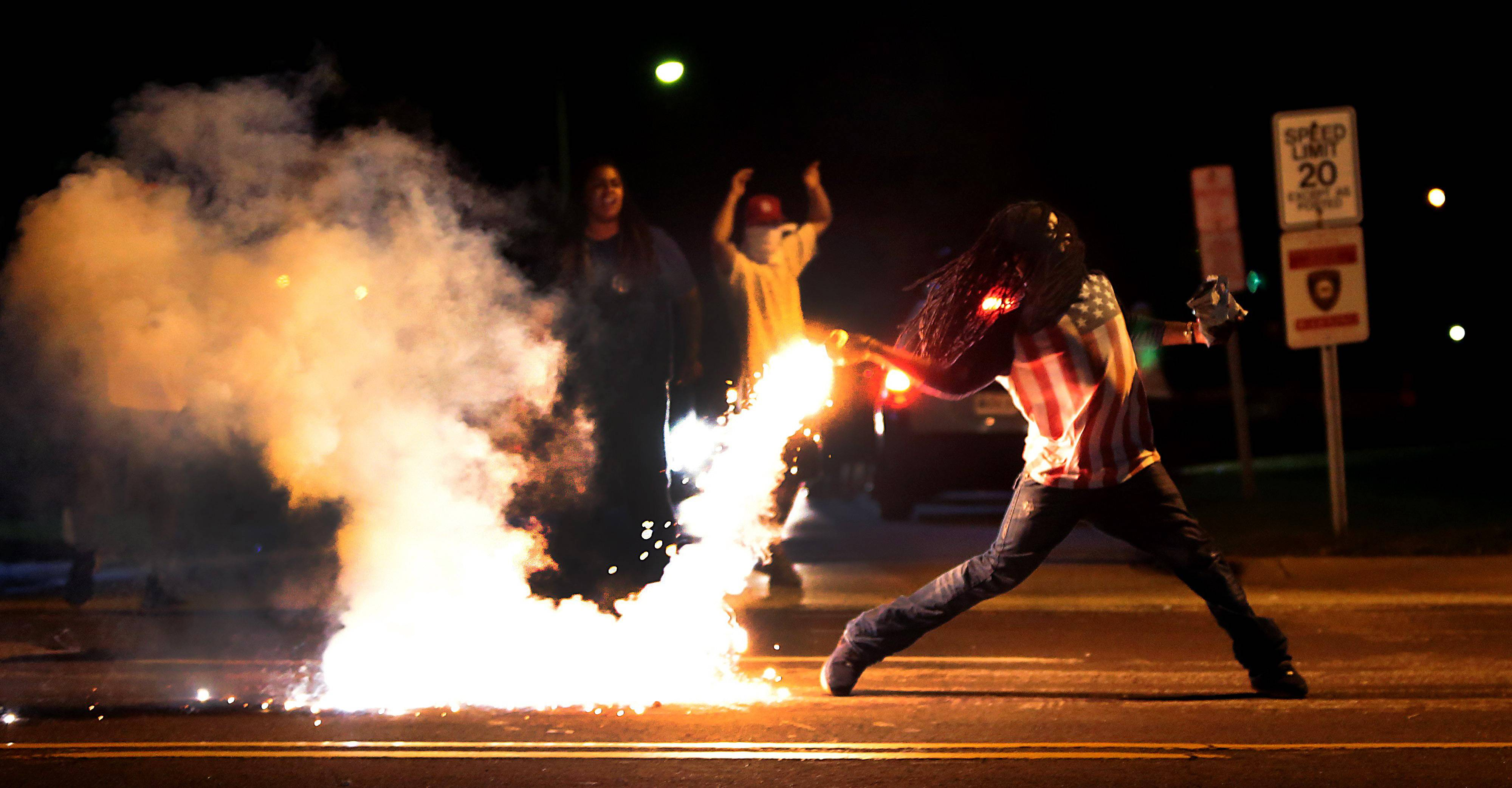 A demonstrator throws back a tear gas container after tactical officers try to break up a group of bystanders Wednesday in West Florissant, Mo. Ferguson has been the site of nightly protests and unrest since 18-year-old Michael Brown was killed during a confrontation with an officer on Saturday.
