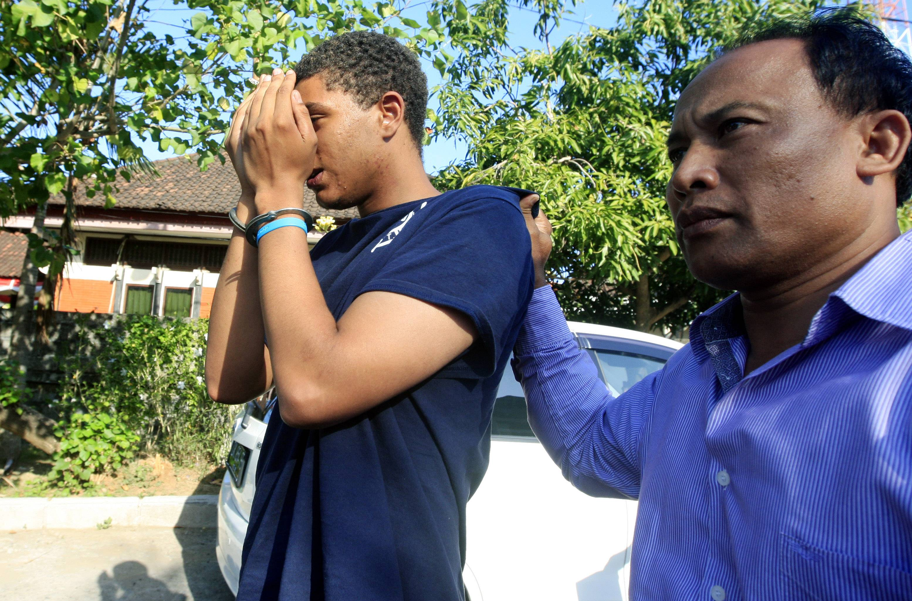 An Indonesian police officer escorts Tommy Schaefer, left, as he is brought Wednesday to a police station for questioning in relation to the death of his girlfriend's mother, in Bali, Indonesia. The body of a 62-year-old American woman was found stuffed inside a suitcase on the Indonesian resort island of Bali. Police arrested Schaefer and Heather Mack, the victim's daughter, in relation to the death. Sheila von Wiese Mack's body was found Tuesday inside the trunk of a taxi parked in front of an upscale hotel in Bali's Nusa Dua area.