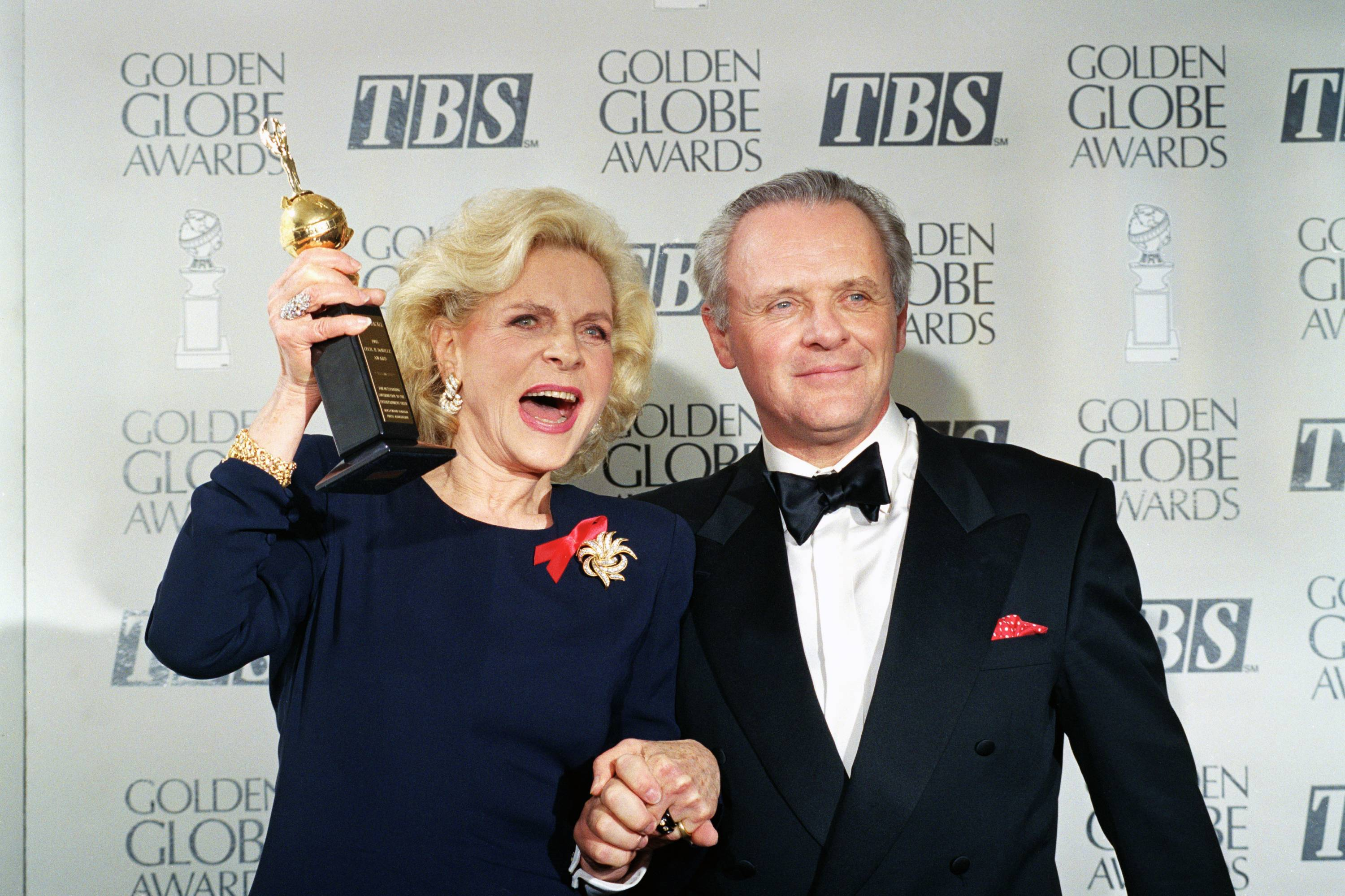 Lauren Bacall holds up her Cecil B. DeMille Award for Lifetime Achievement as she holds hands with actor Anthony Hopkins backstage at the 50th annual Golden Globe Awards in 1993. Bacall died Tuesday in New York.