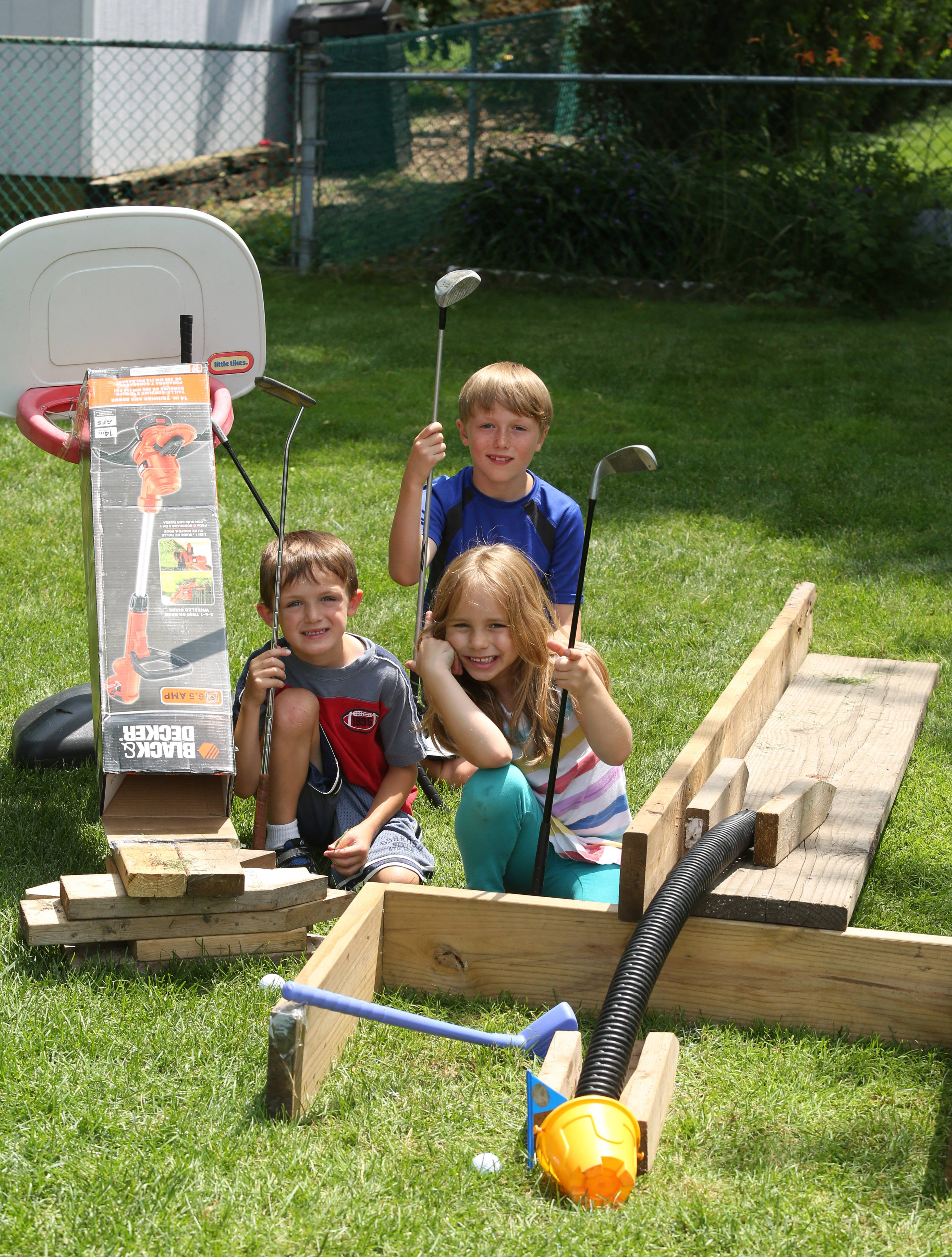 Rylan Williams, 9, background, his brother Caden, 5, left, and friend Lily Anderson, 6, created a homemade mini-golf course made out of boards, a basketball hoop, tubes, buckets, and other items in the Williamses backyard in Schaumburg.
