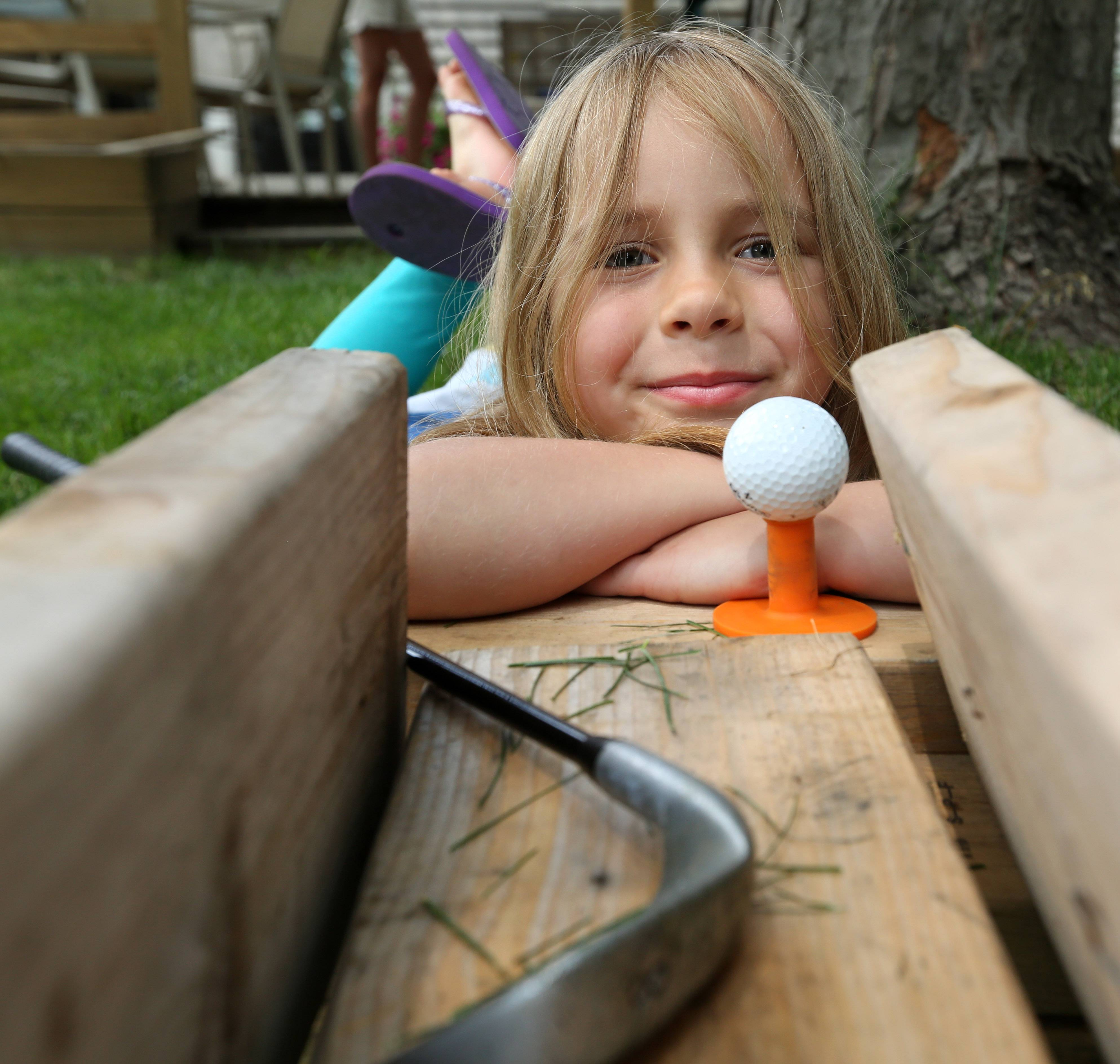 Lily Anderson, 6, helped create a homemade mini golf course made out of boards, a basketball hoop, tubes, buckets, and other items in her friend's backyard in Schaumburg.