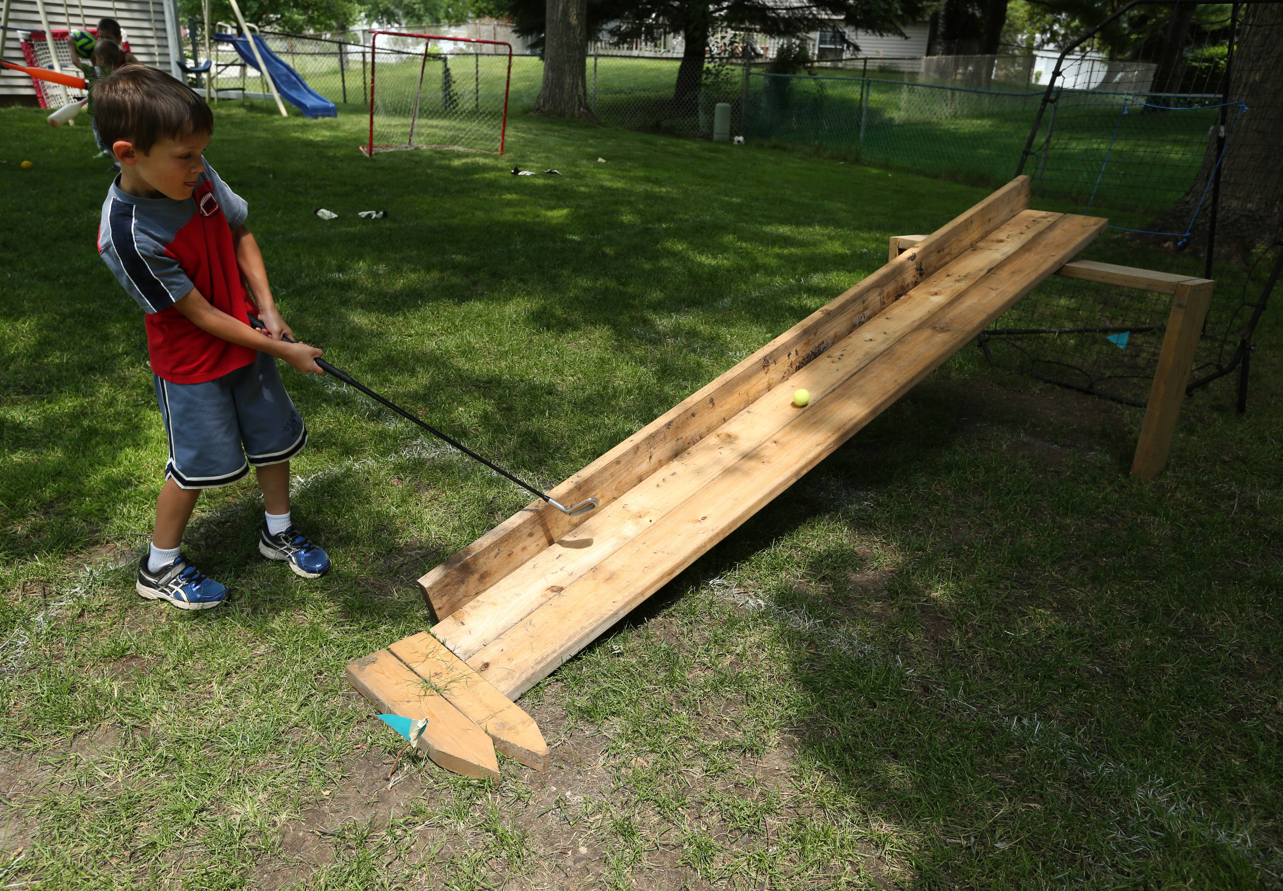 Caden Williams, 5, takes a swing on a hole requiring the ball to travel up a wooden path before dropping into a soccer net.