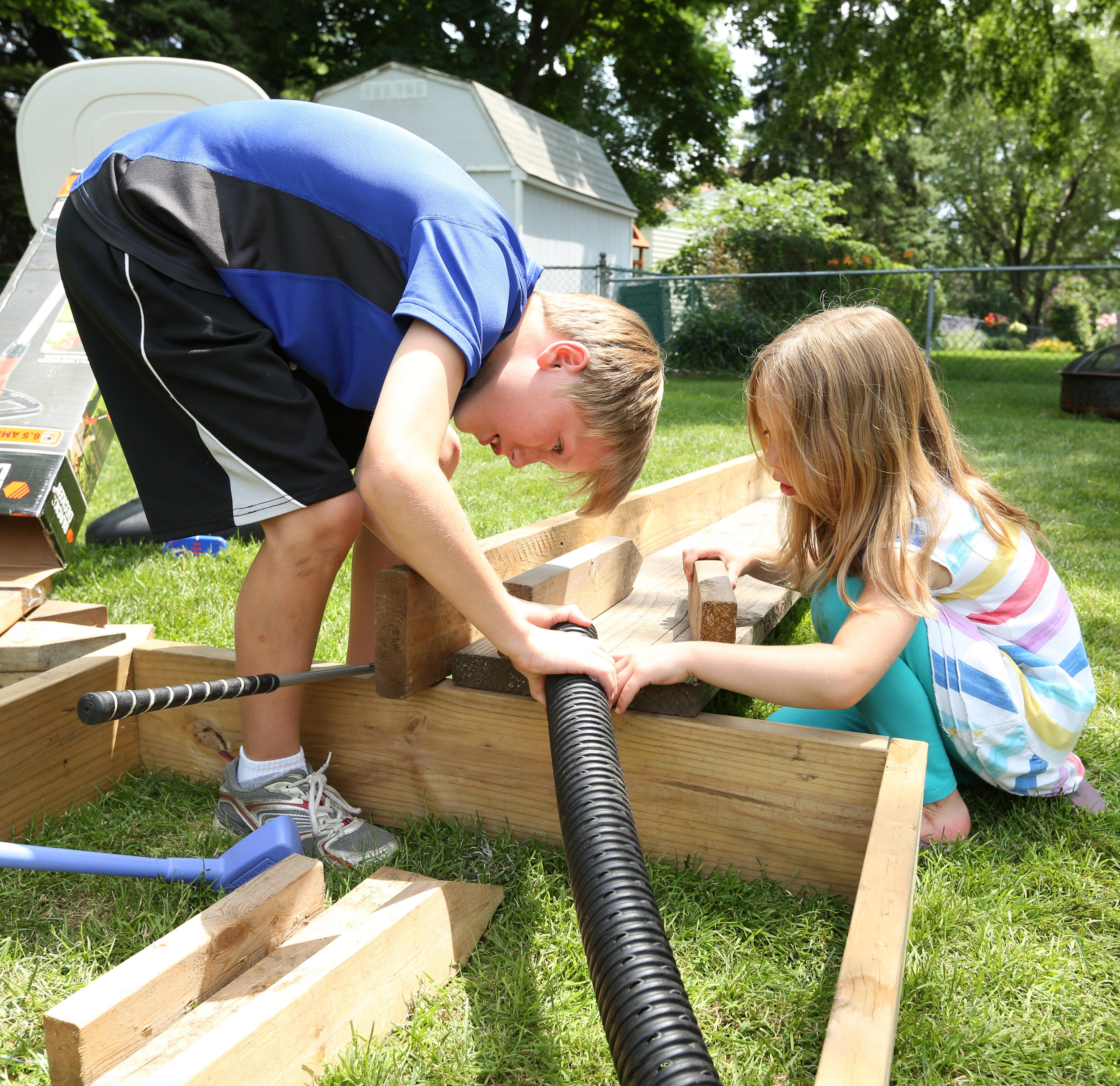 Rylan Williams, 9, left, and friend Lily Anderson, 6, work with tubing and lumber to create one of the holes in their mini-golf course.