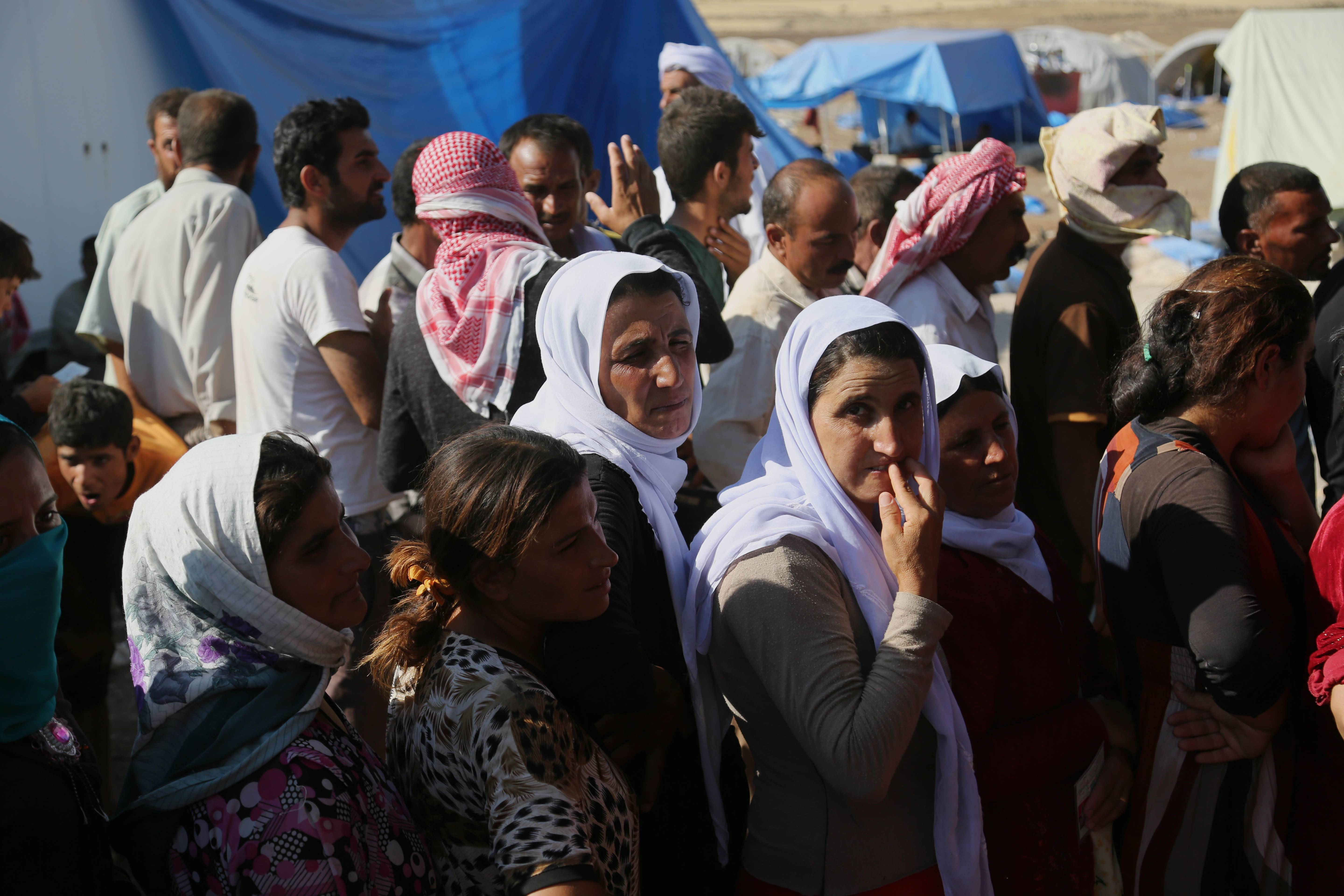 Displaced Iraqis from the Yazidi community gather for humanitarian aid at Nowruz camp, in Derike, Syria, Tuesday.