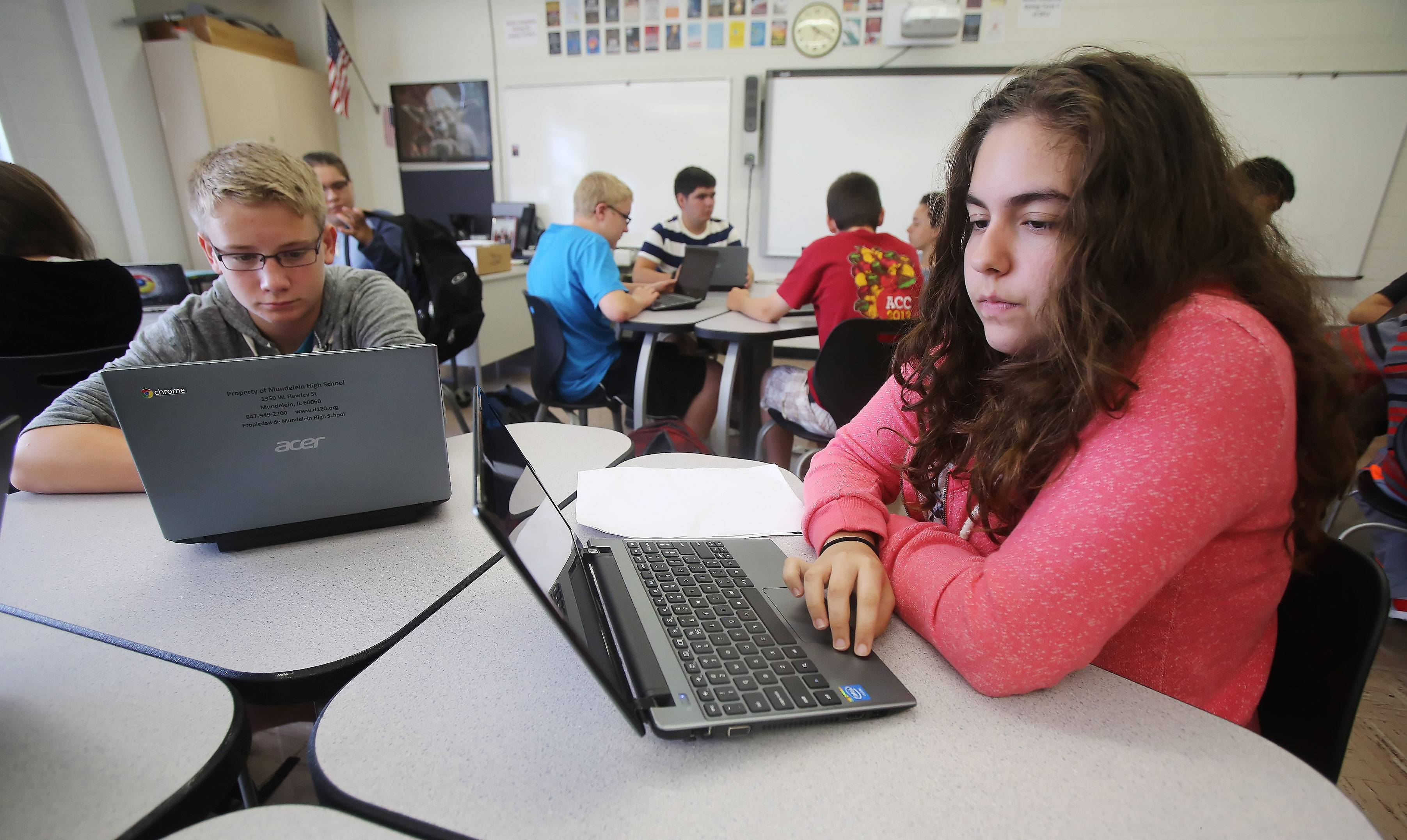 Mundelein High School freshmen Breanna Giametta, right, and Carson Bernett work on their new Chromebooks in Algebra I class on the first day of school Wednesday. The school is giving each student a Chromebook laptop to work with this year as part of a new program.