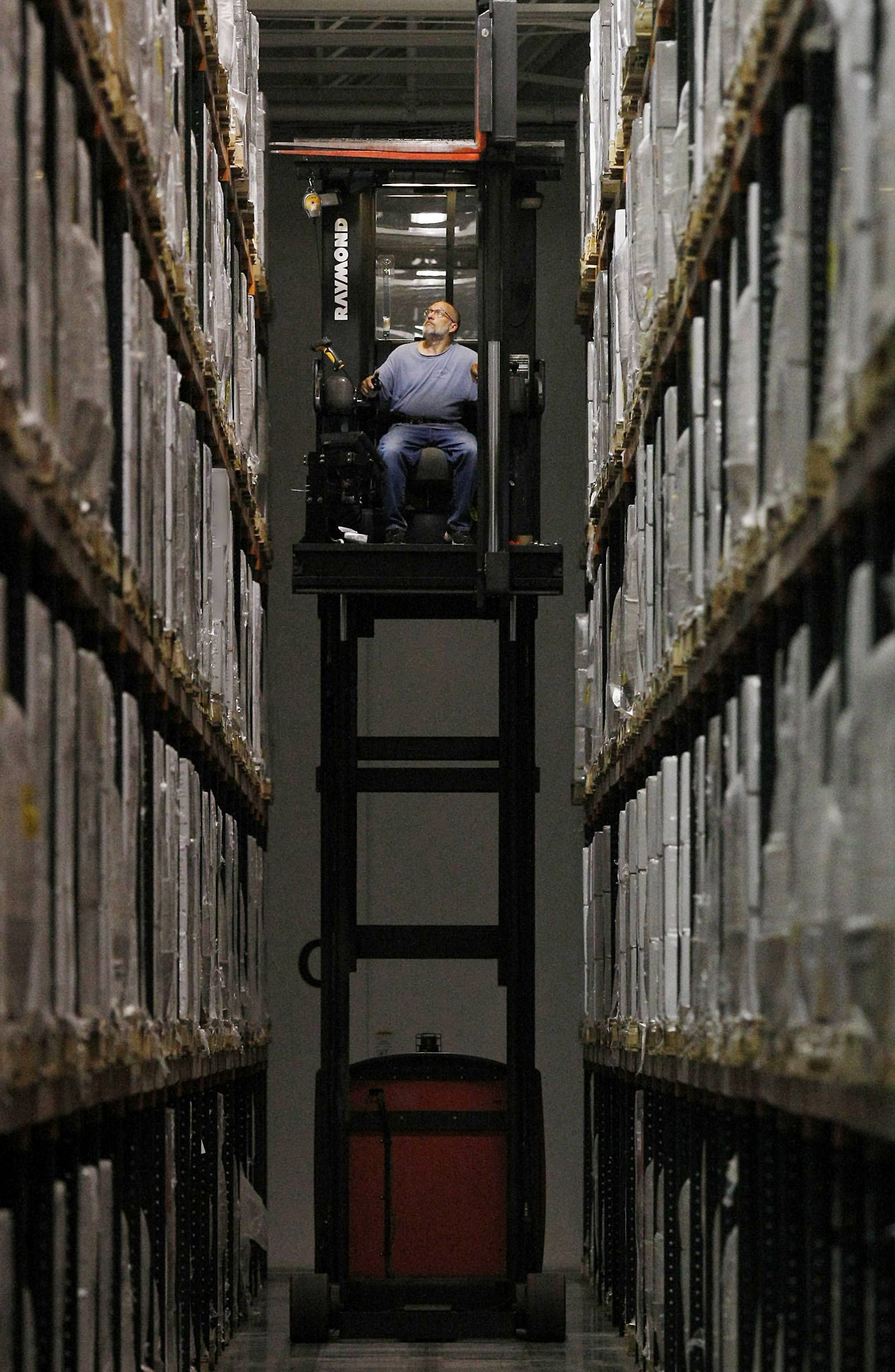 Warehouseman Harry Michael operates a narrow aisle fork lift retrieving boxes for a fork truck driver to load into a semi-trailer at Parke Warehouse in Decatur.