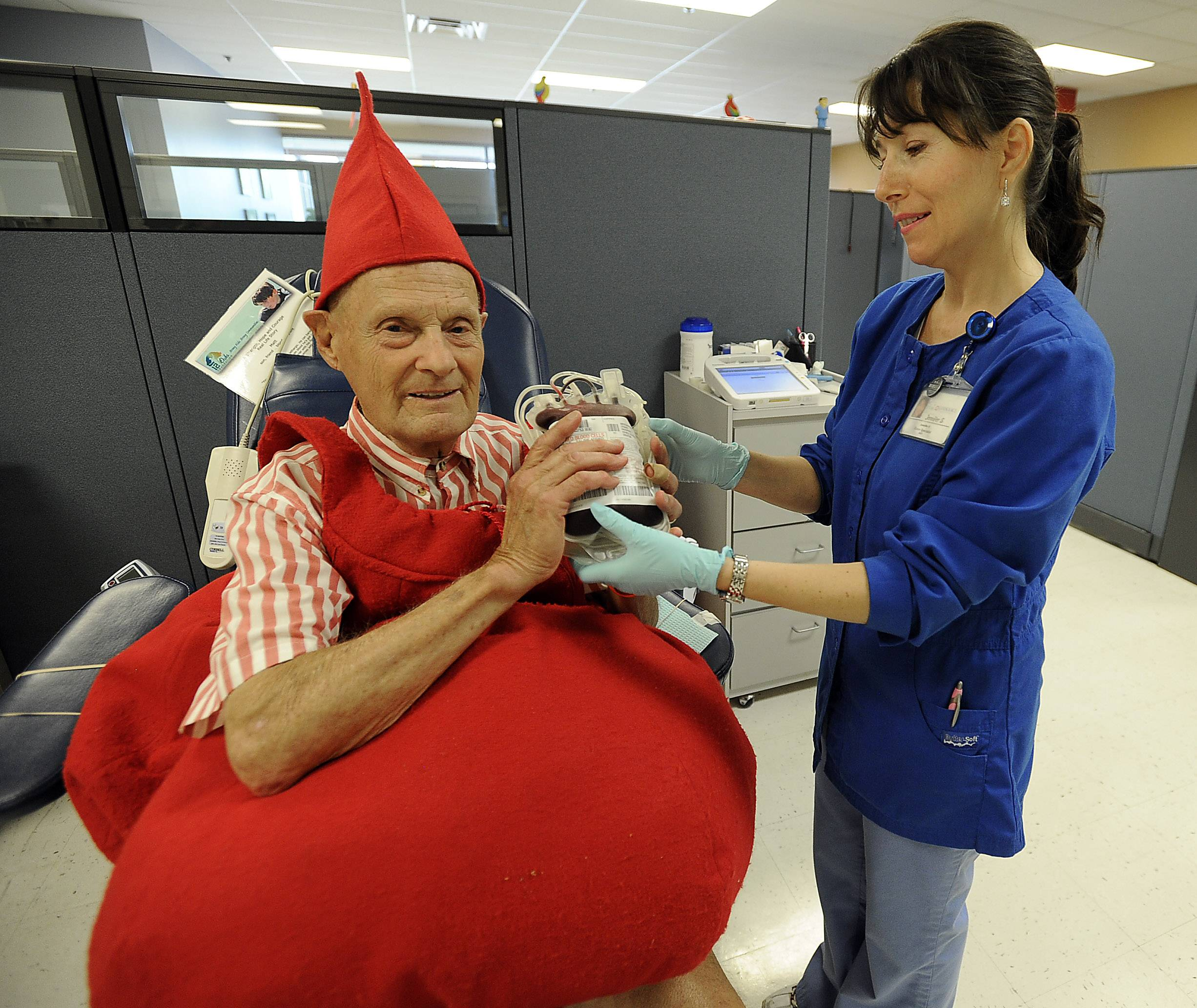 "Palatine resident George Serena, aka ""Mr. Blood Drop,"" holds his 151st blood donation at LifeSource in Arlington Heights. Phlebotomist Jennifer Sava, right, performed the procedure Tuesday."
